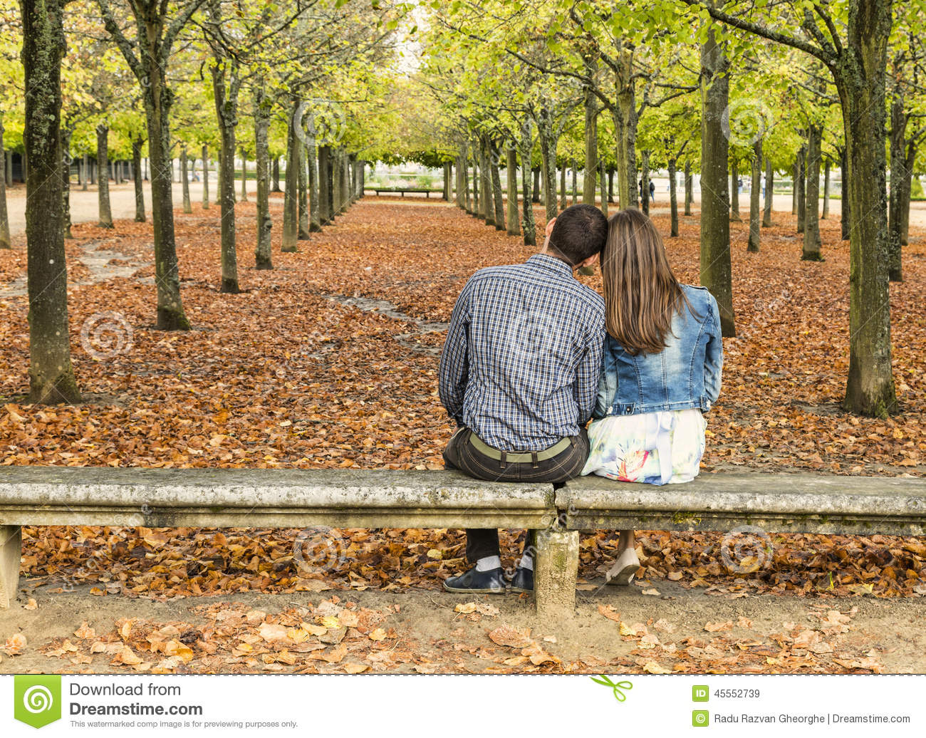 Young Couple Sitting On A Bench In A Park In Autumn Stock