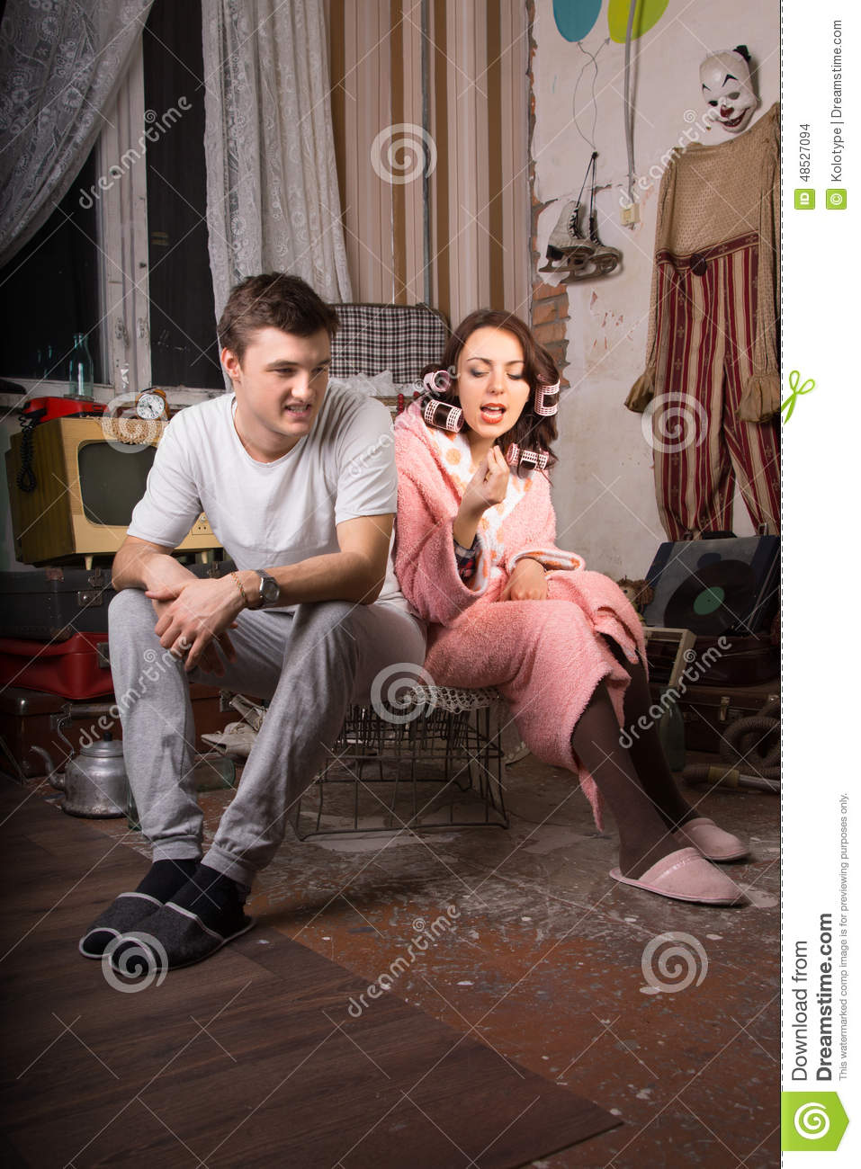 Young Couple Sitting on Cage at Messy Room