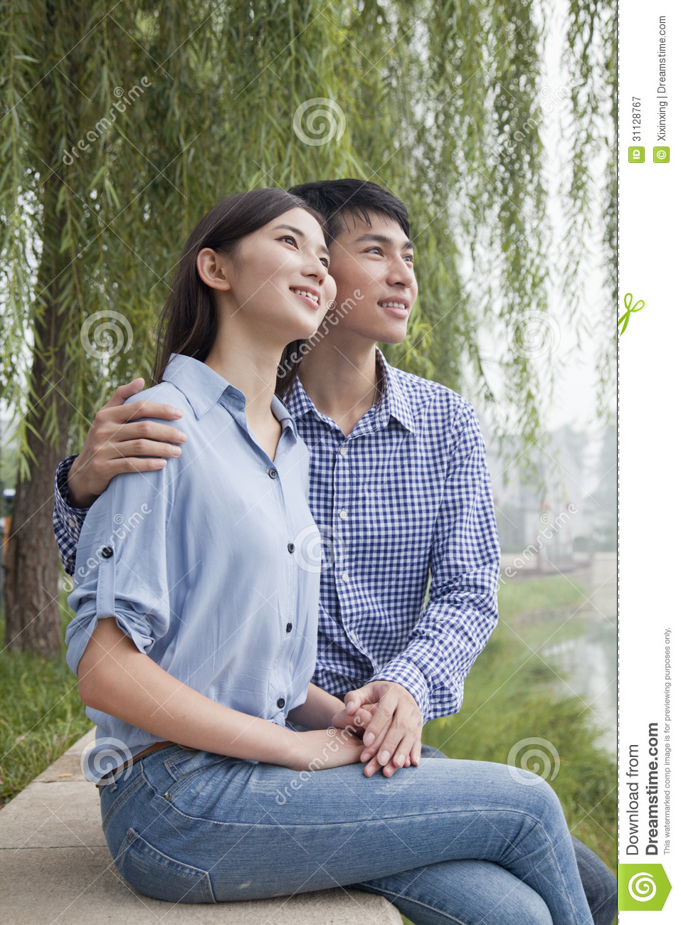 Young Couple Sitting By A Canal, Arm Around Shoulder ...