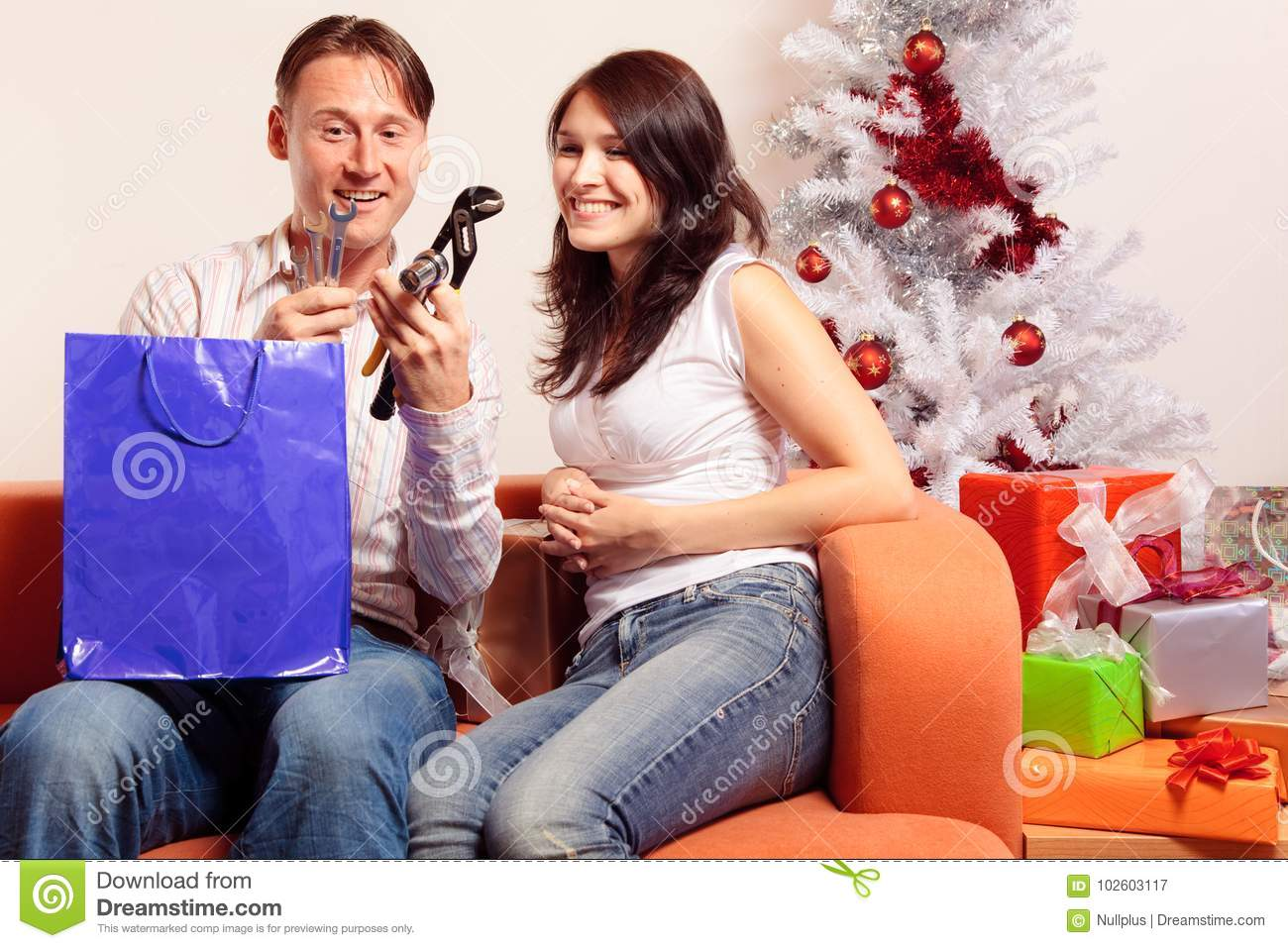 young couple exchanging christmas gifts