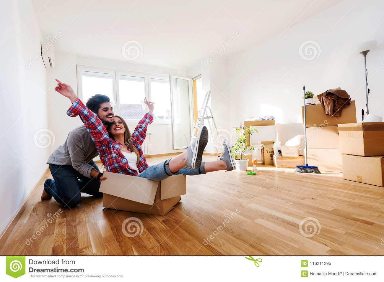 Young couple sitting on the floor of empty apartment. Move in to new home.