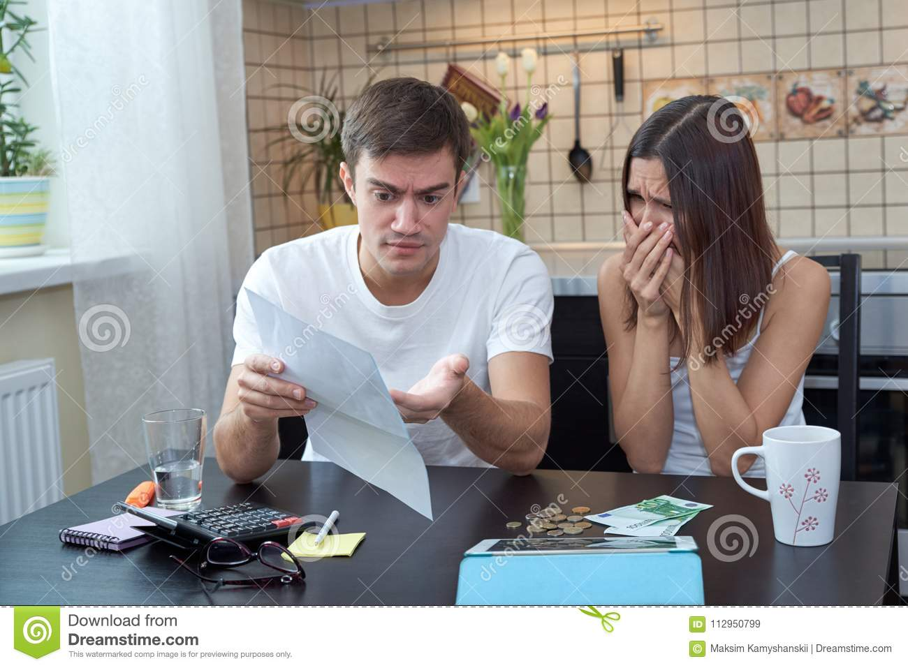 A young couple sitting in the kitchen planning and analyzing the family budget. Financial difficulties, negative emotions