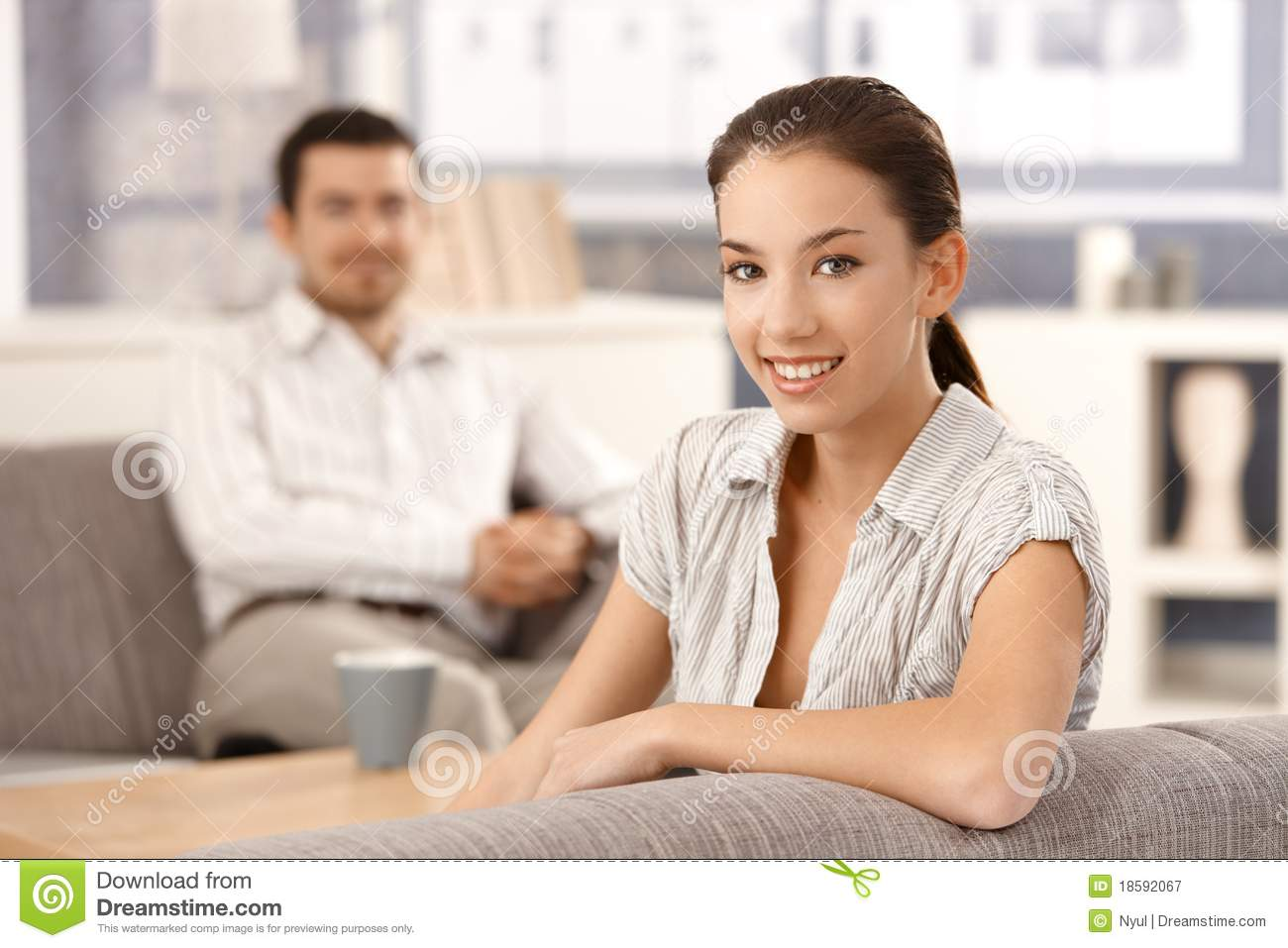 Young couple sitting in living room at home royalty free for Young couple living room ideas