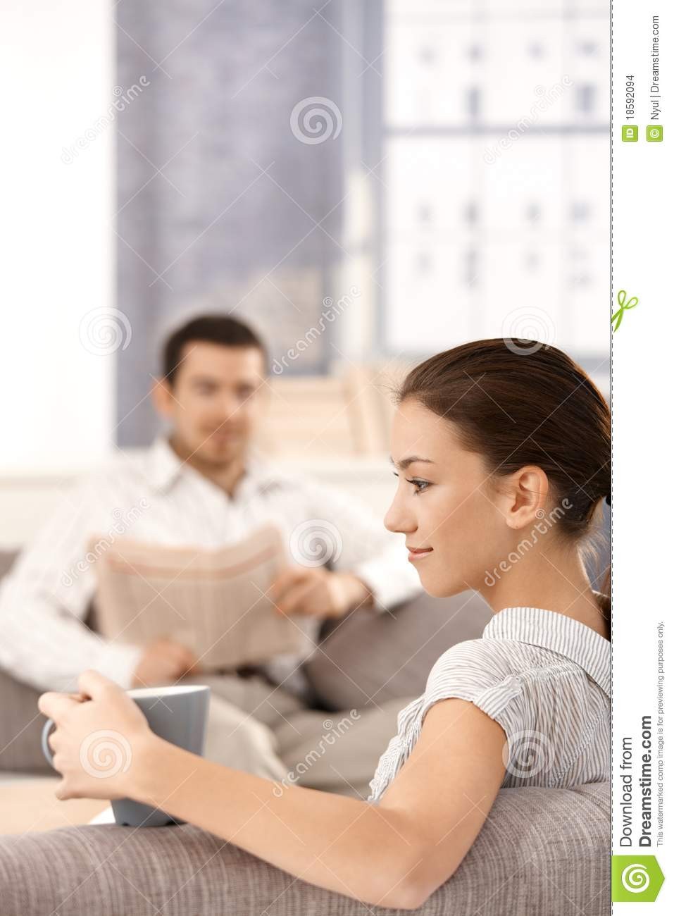 Young couple sitting in living room at home stock images for Young couple living room ideas