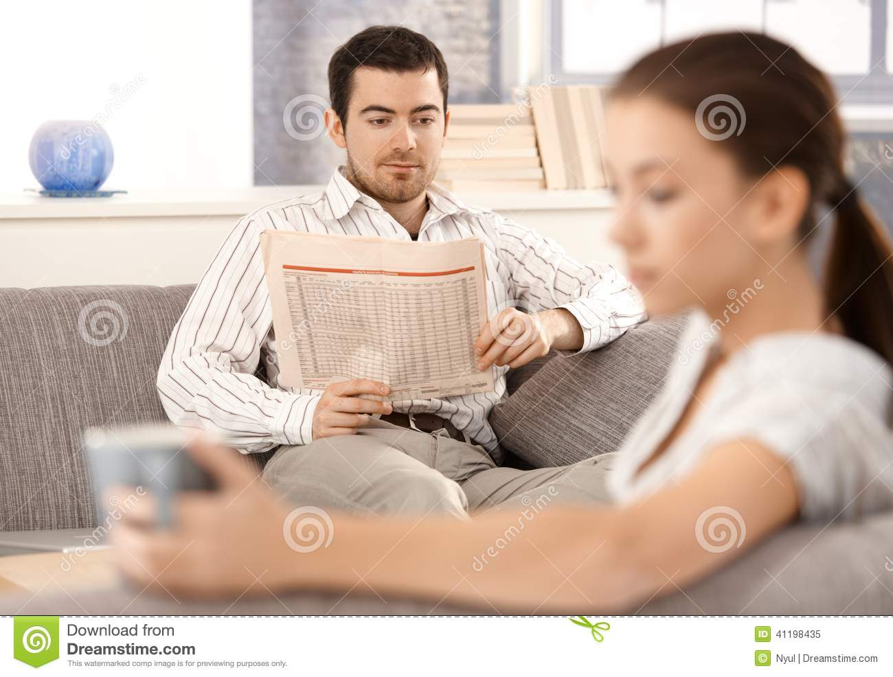 Young couple sitting separated in living room stock photo for Living room ideas young couples