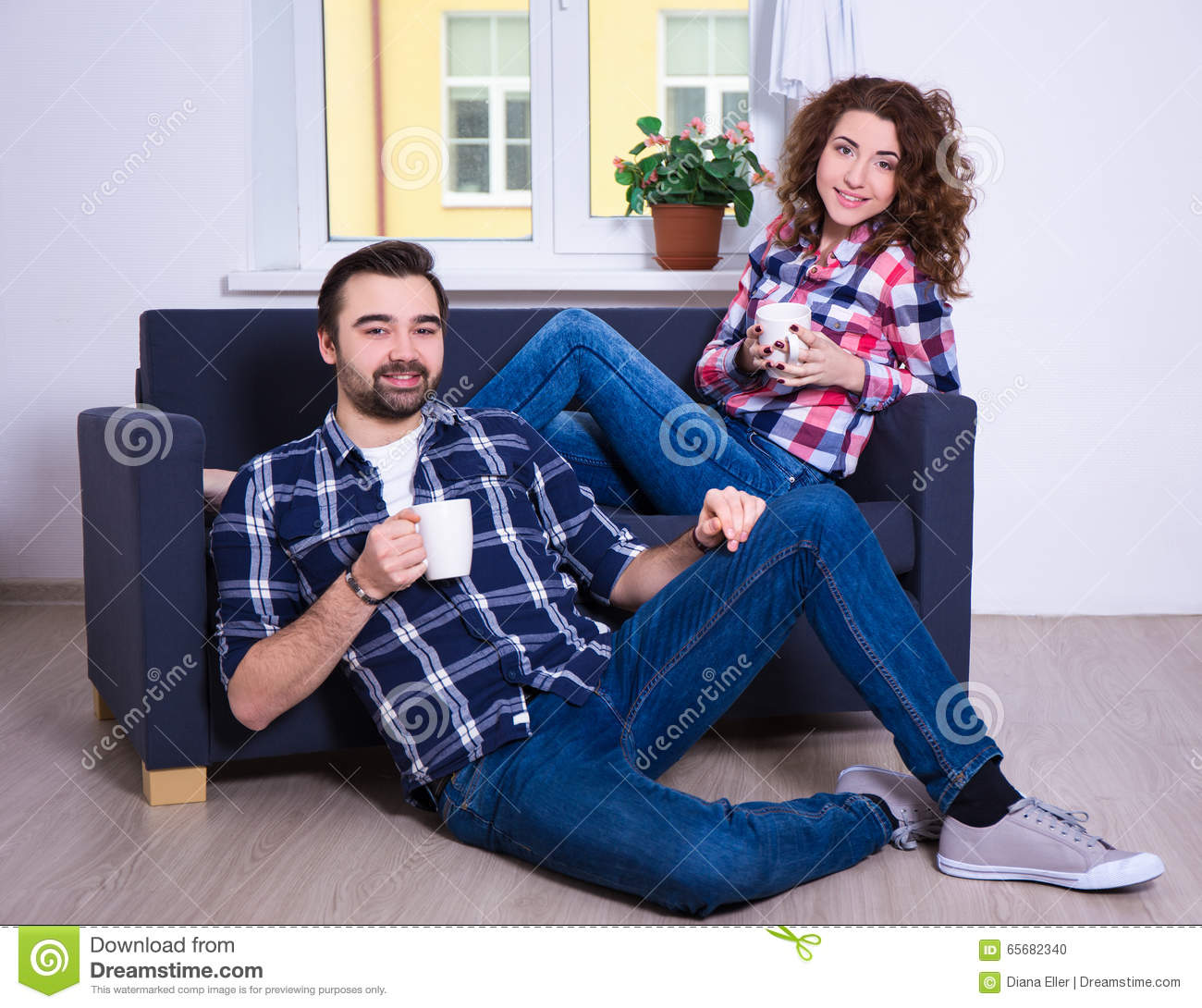 Young couple sitting on sofa with cups of tea or coffee in for Young couple living room ideas