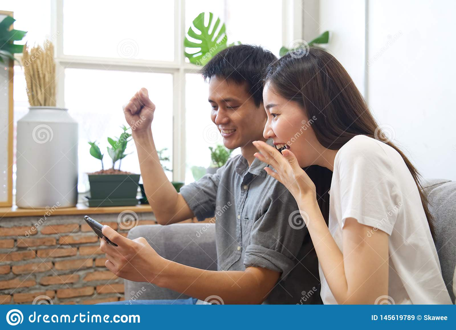 Young couple sitting on sofa are watching mobile phone and feeling surprise&happy.