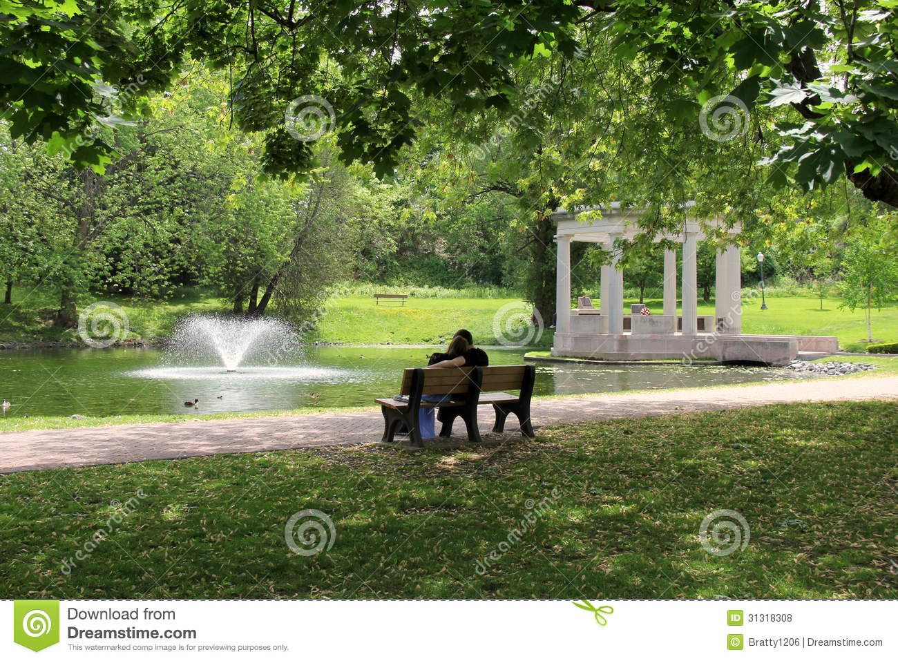 Young couple sitting together on old park bench under shade tree with ...