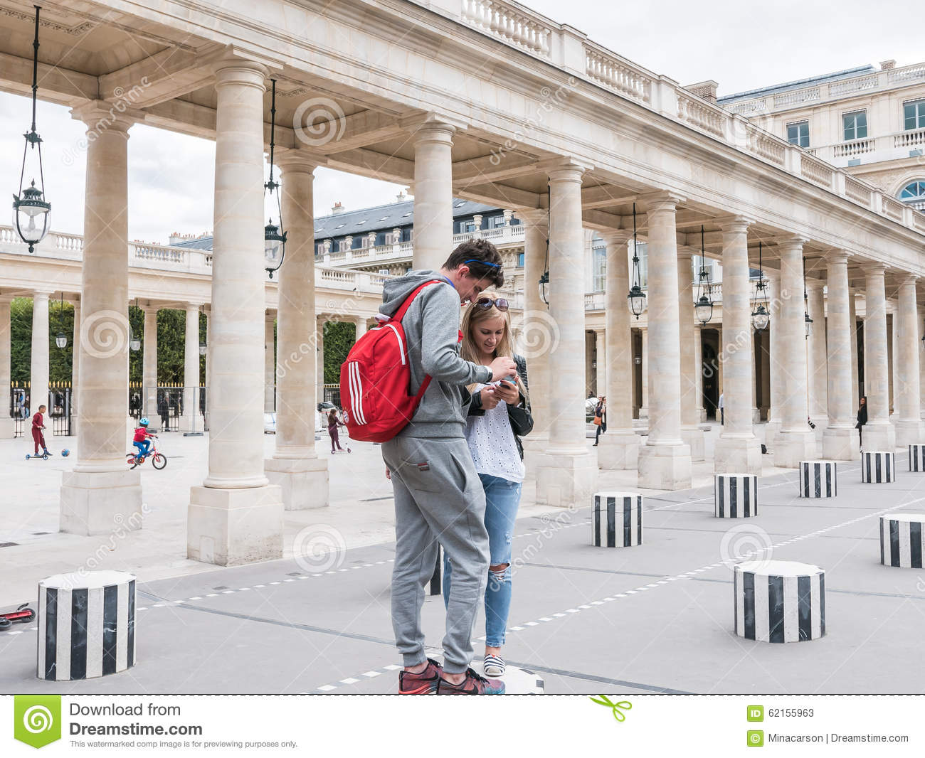 Young couple smiles at smart phone at Palais Royal, Paris
