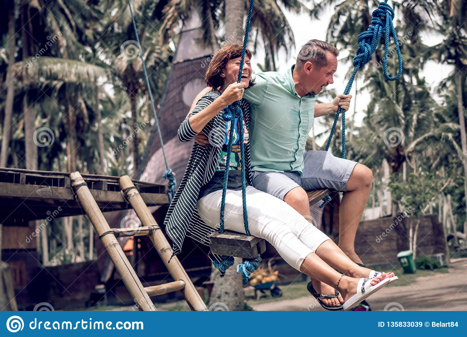 young couple swinging info