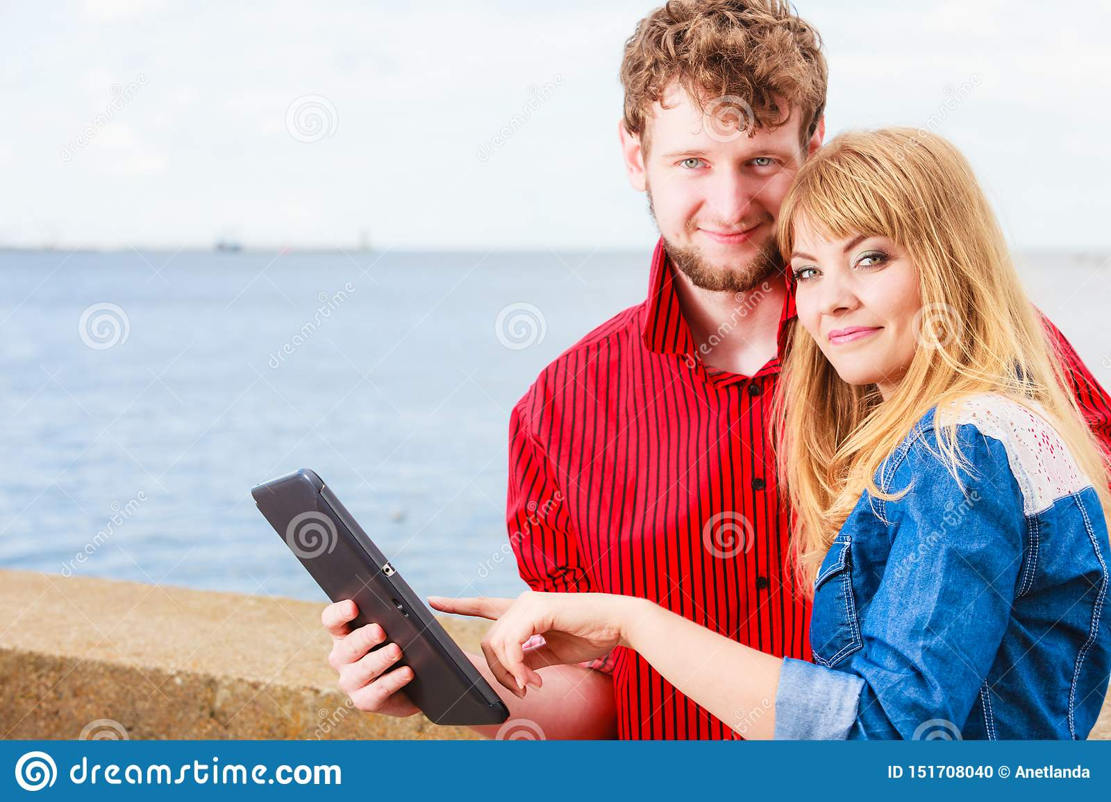 Young couple with tablet by seaside outdoor