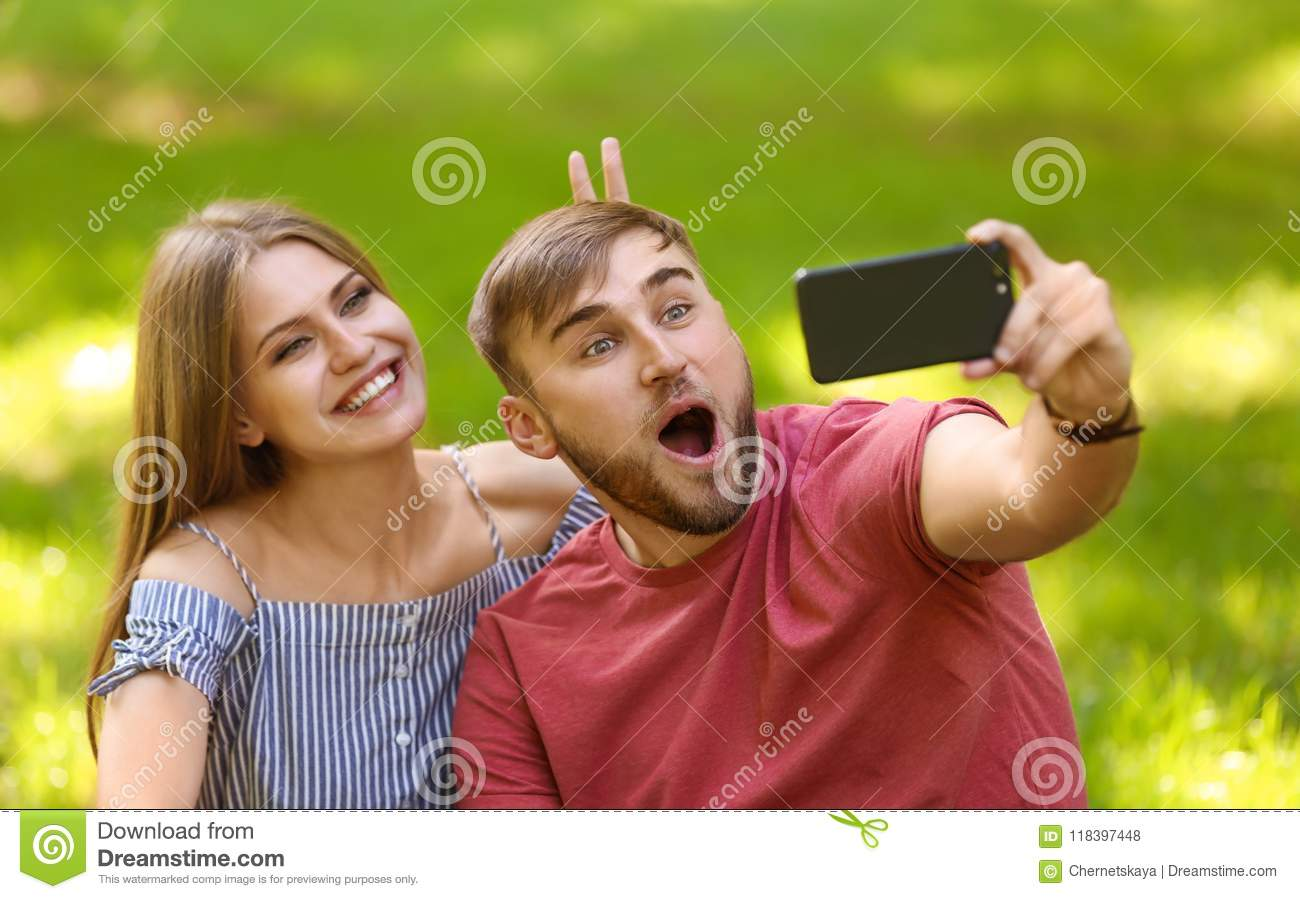Young couple taking selfie on green grass in park