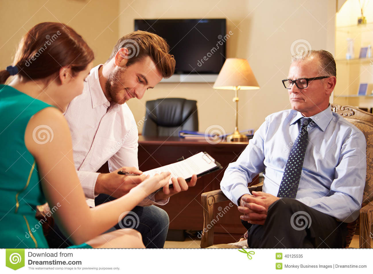 Young Couple Talking To Financial Advisor In Office