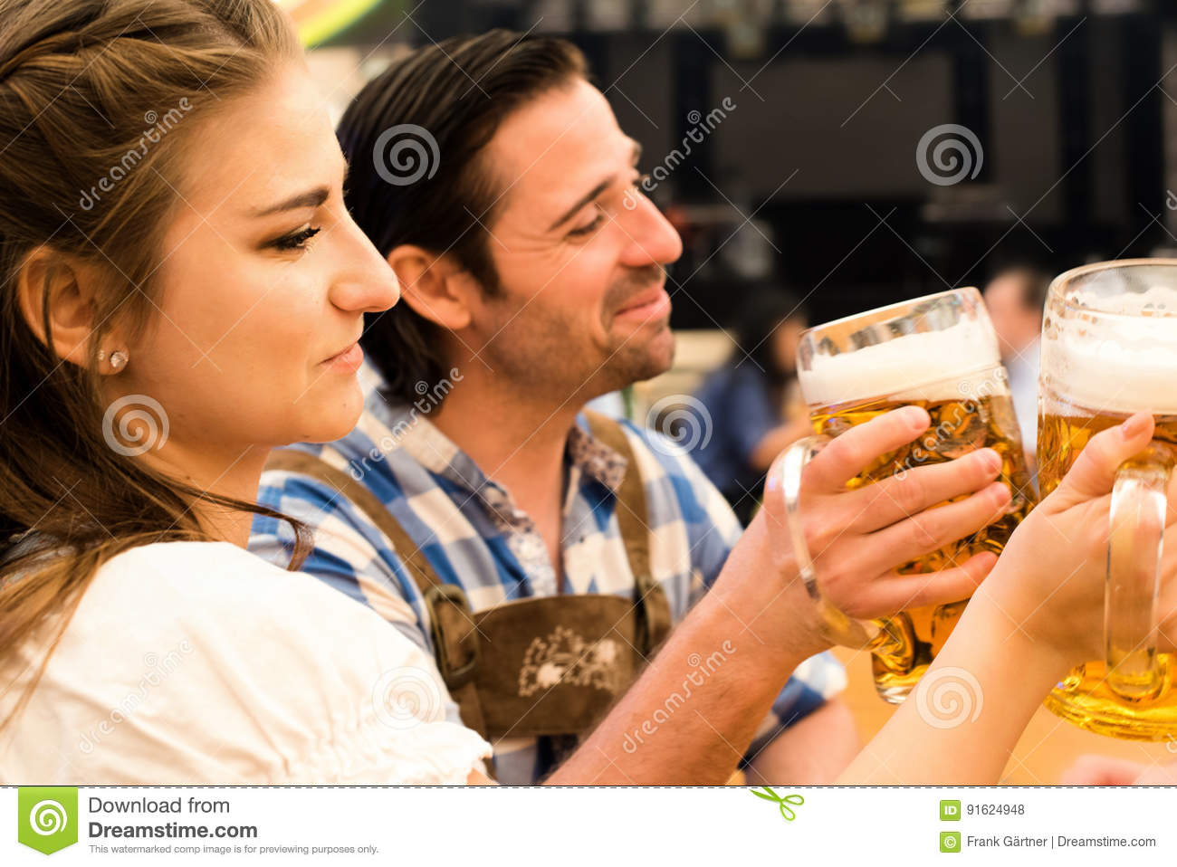 Young couple toasting in Oktoberfest beer tent