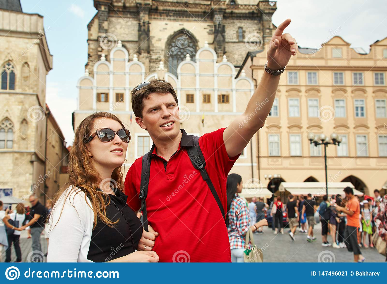 Young couple travelers walking on a street of European city. sightseeing traveler. Prague, Old Town Square.