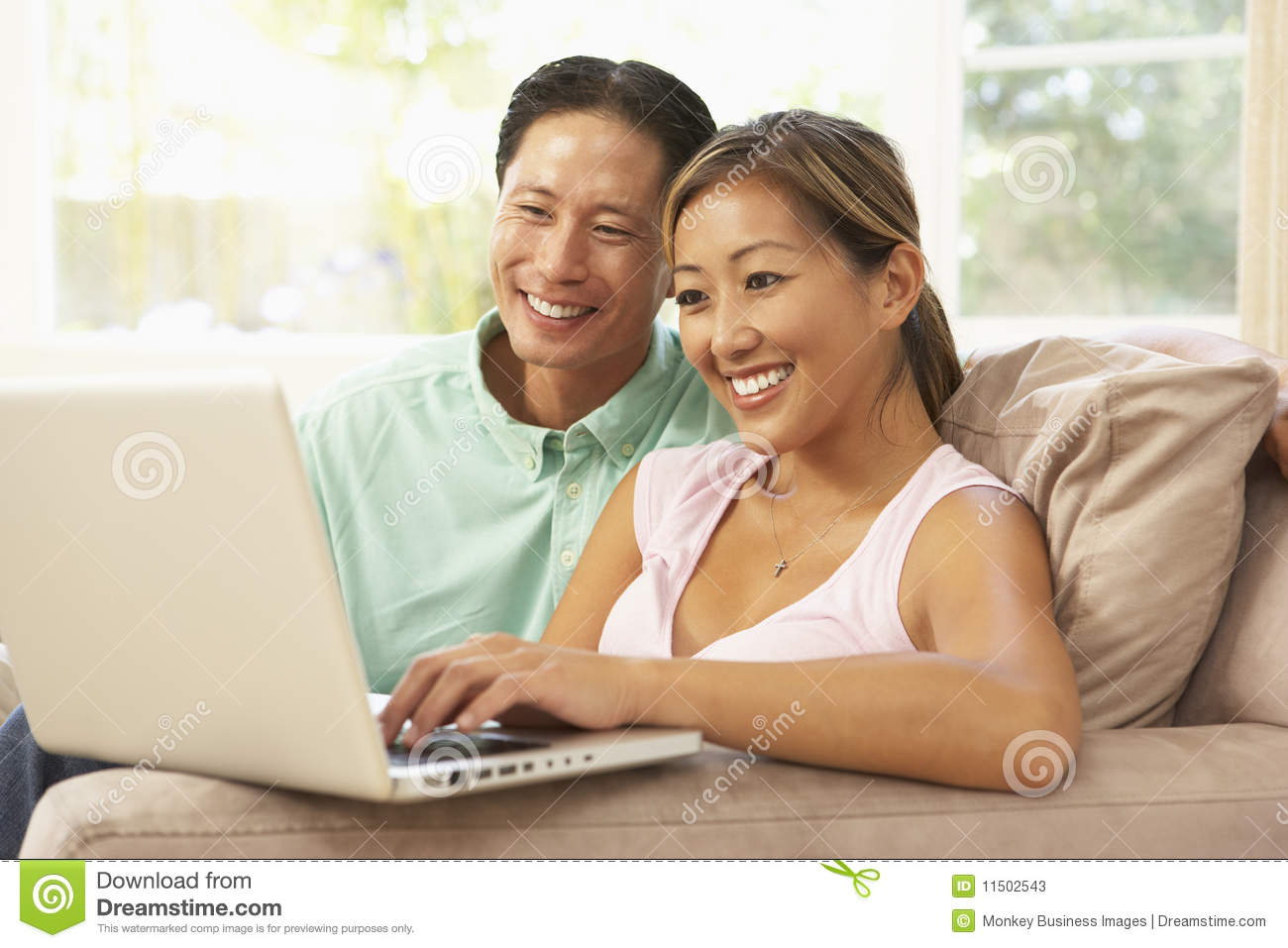 Young couple using laptop at home stock photos image for Household bargaining and the design of couples income taxation