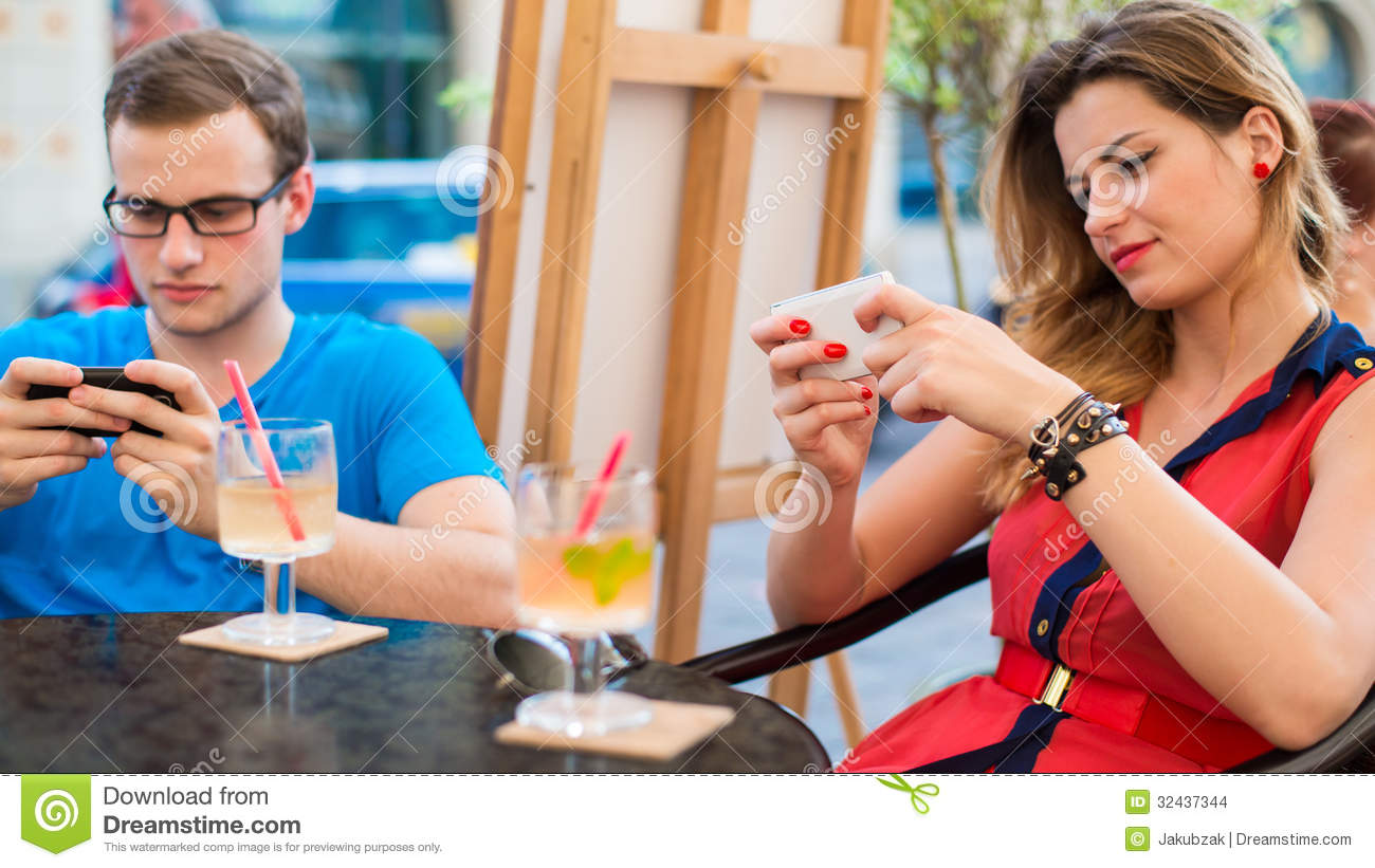 Young Couple Using Mobile Phones In A Cafe. Stock Images - Image ...