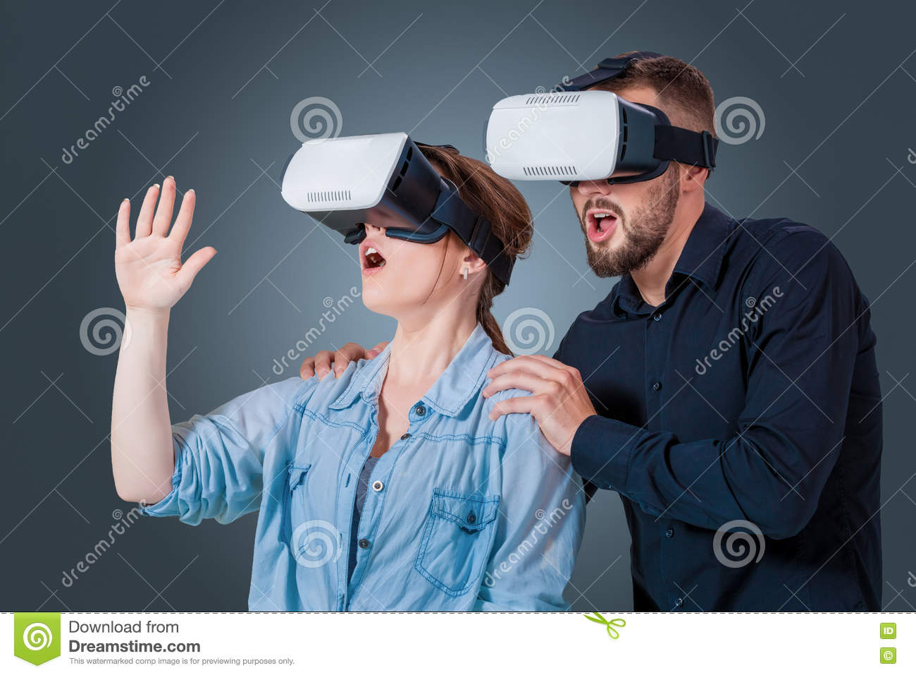 a4c4e951ec6e Excited young couple using a VR headset glasses and experiencing virtual  reality on grey blue background