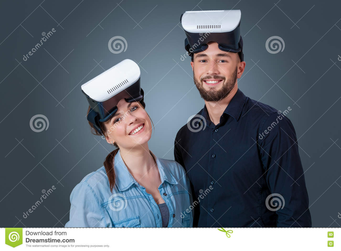 e22444b4241d Excited young couple using a VR headset glasses and experiencing virtual  reality on grey blue background. Looking at the camera