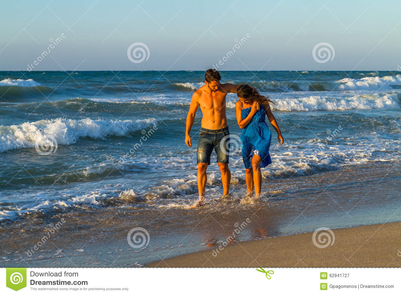 Happy young couple in jean shorts and a blue dress, having fun walking  along a sandy beach at dusk, getting wet, teasing and embracing one another.