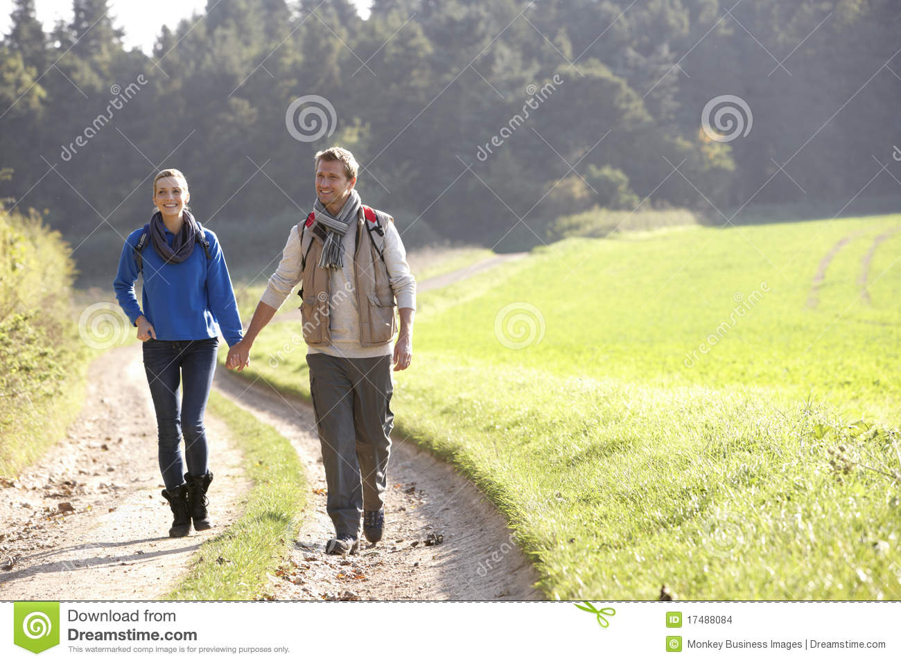 Young couple walking in park holding hands smiling Young Couple Walking In The Park