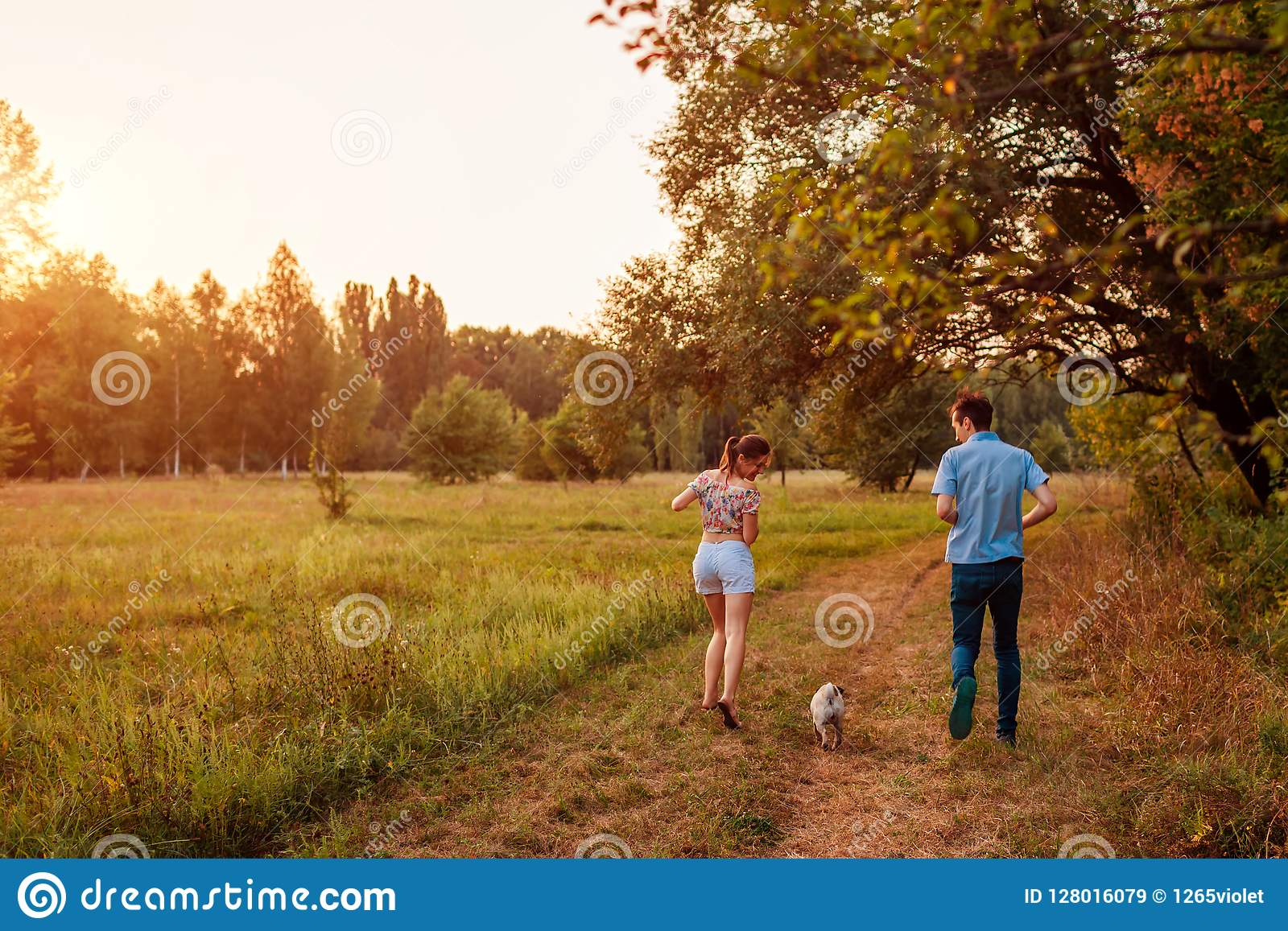 Young couple walking pug dog in autumn forest. Happy puppy running along and having fun playing with master.
