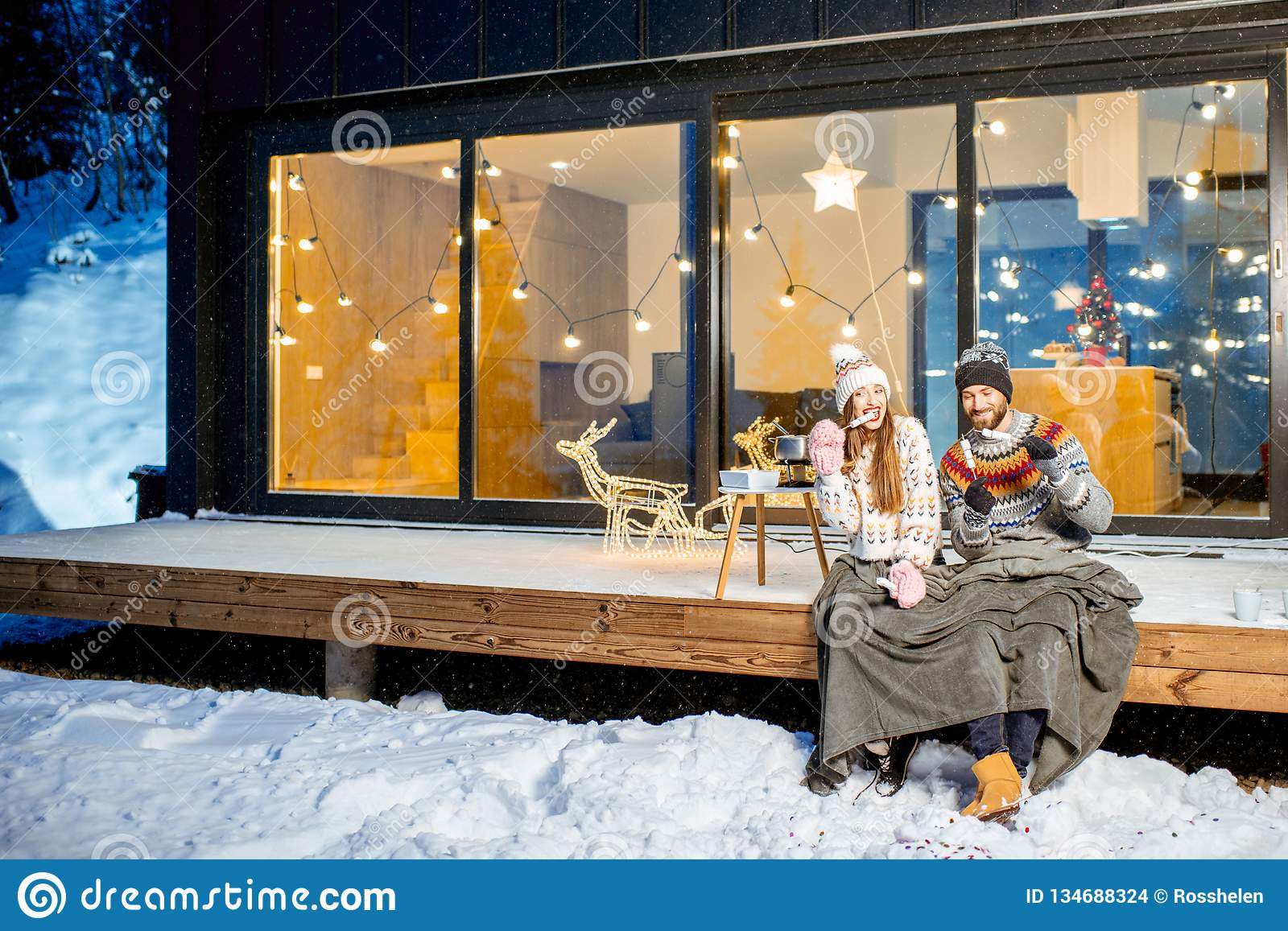 Couple warming up near the house during the winter holidays