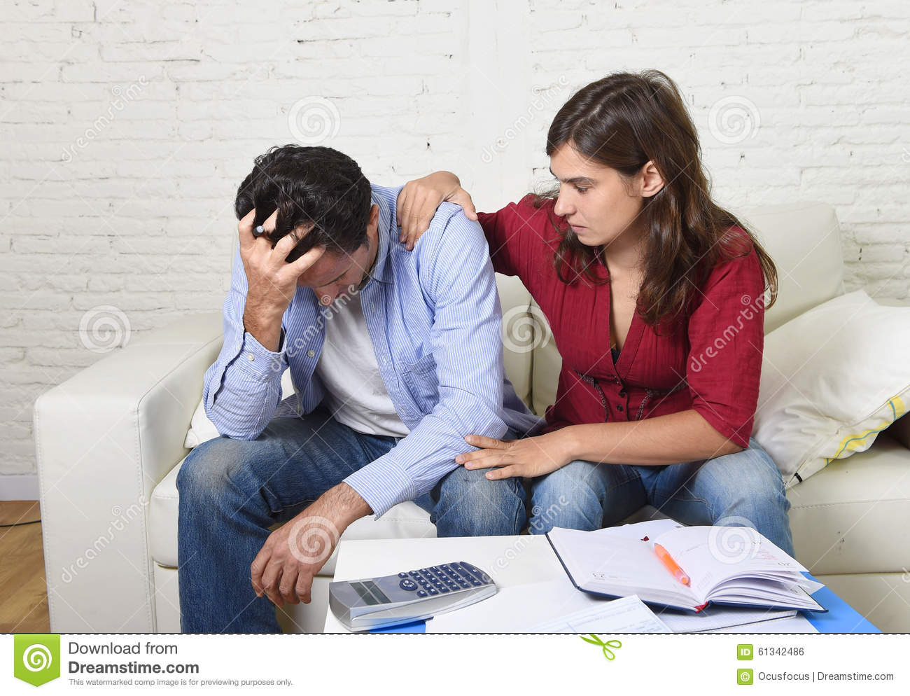 Young couple worried home in stress wife comforting husband accounting debt unpaid bills bank papers expenses