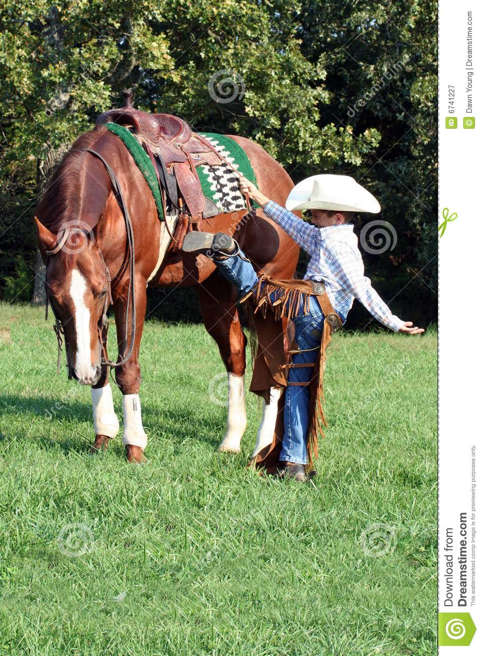 Young cowboy mounting horse