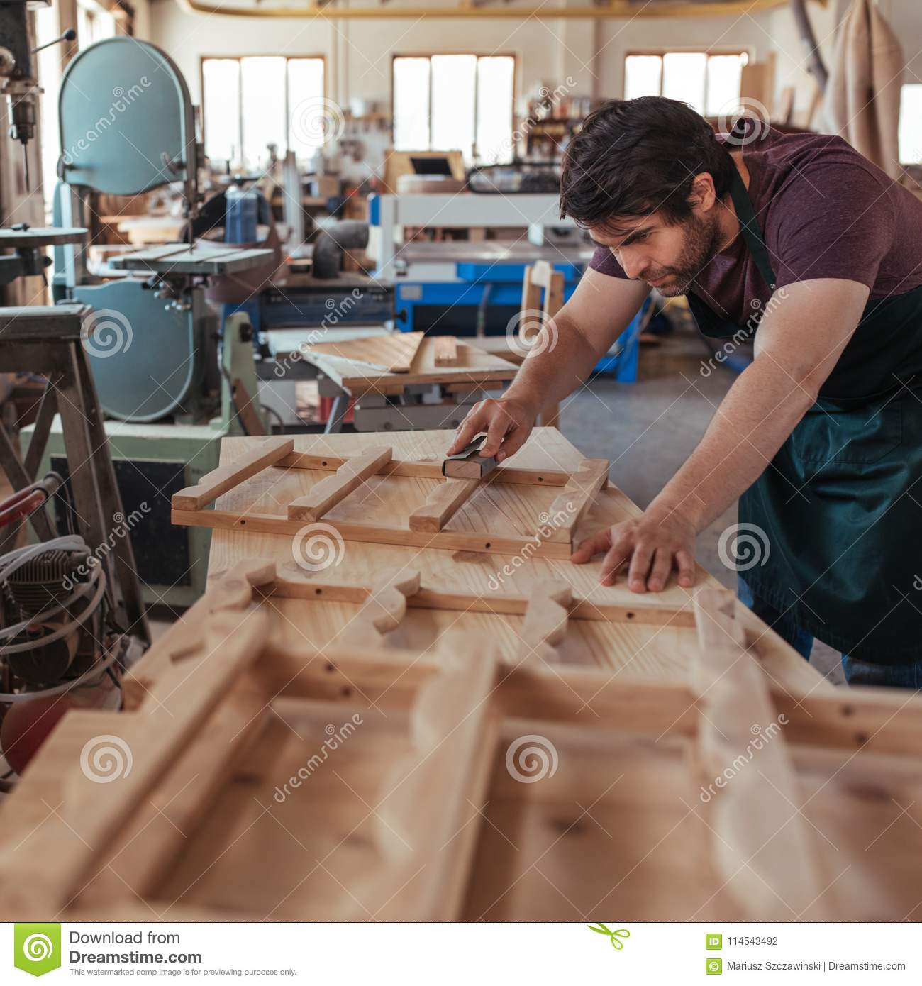 Craftsman Skillfully Sanding Wood While Working In His Carpentry