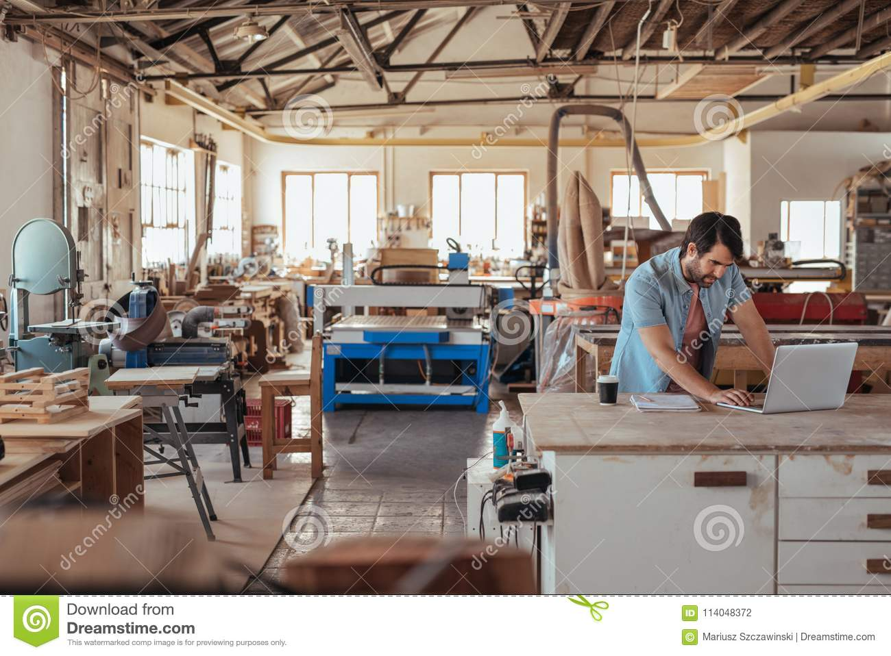 Young Craftsman Working On A Laptop In His Woodworking Studio Stock