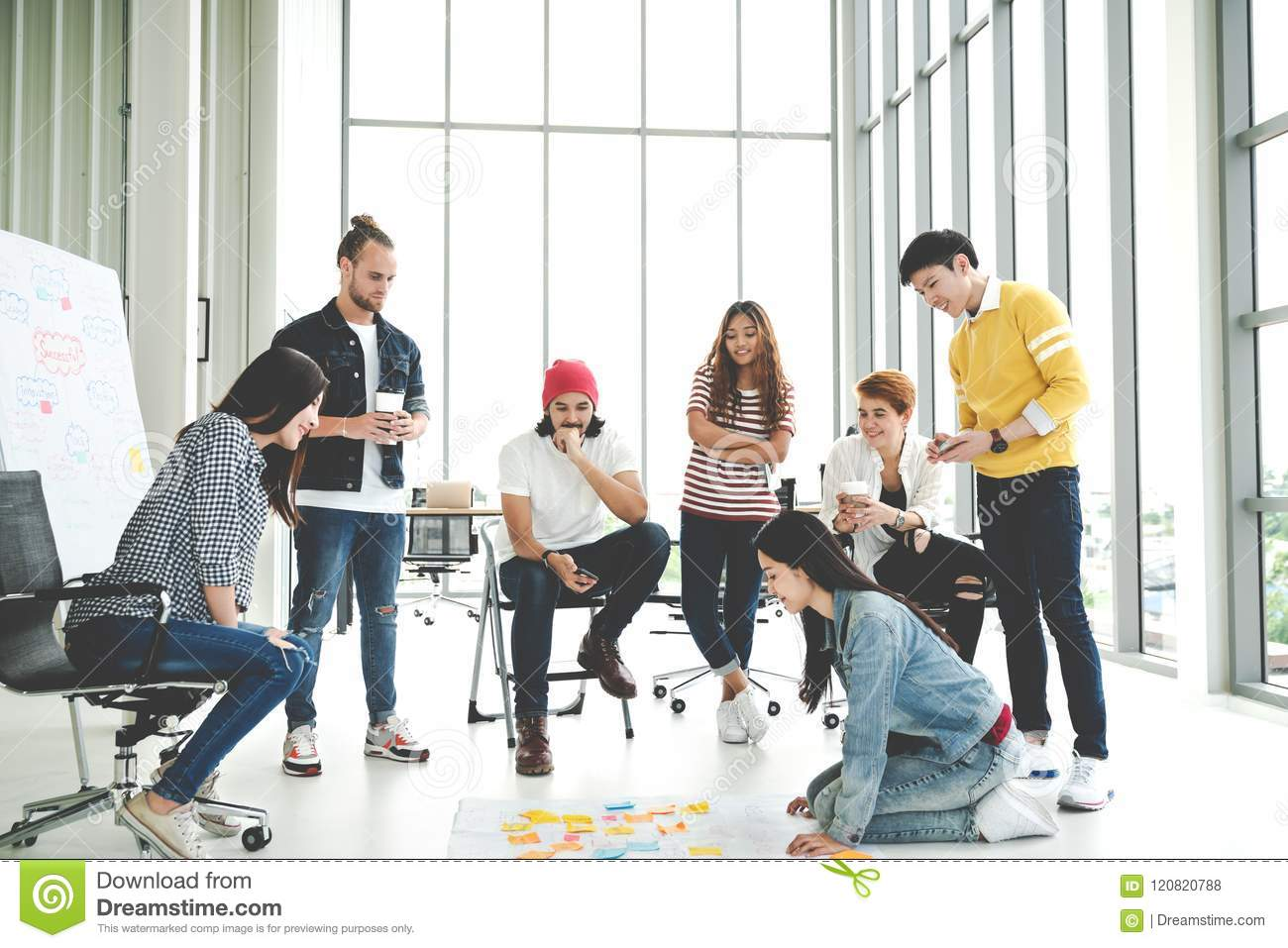 Young creative diverse group meeting and looking at project plan lay out on floor discuss or brainstorm business strategy