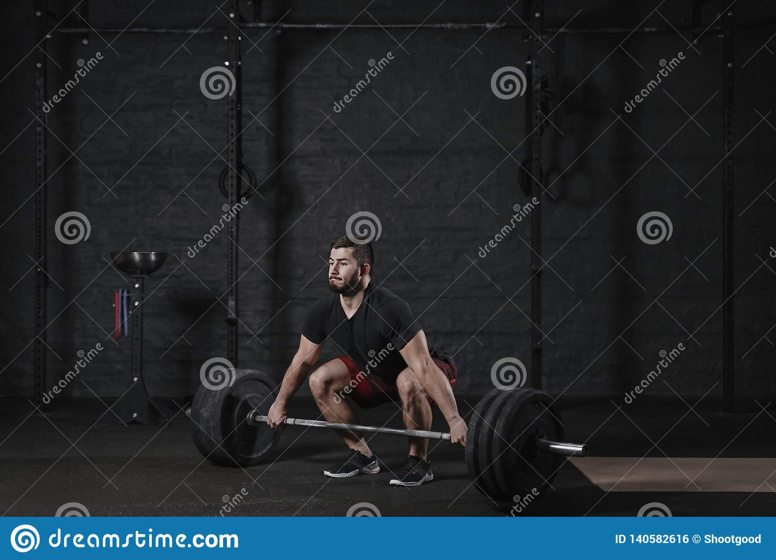 Young crossfit athlete doing deadlift exercise with heavy barbell at gym. Man practicing functional training powerlifting workout
