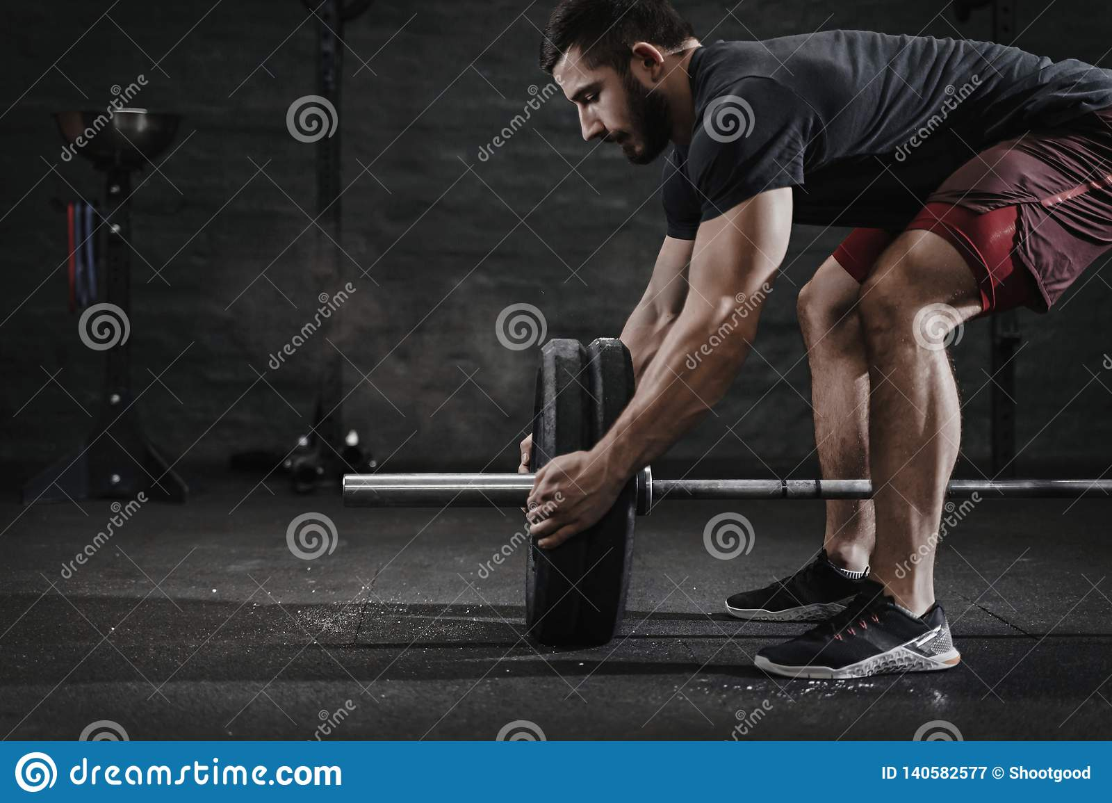 Young crossfit athlete preparing barbell lifting weight at the gym. Magnesia protection dust cloud. Handsome man doing functio