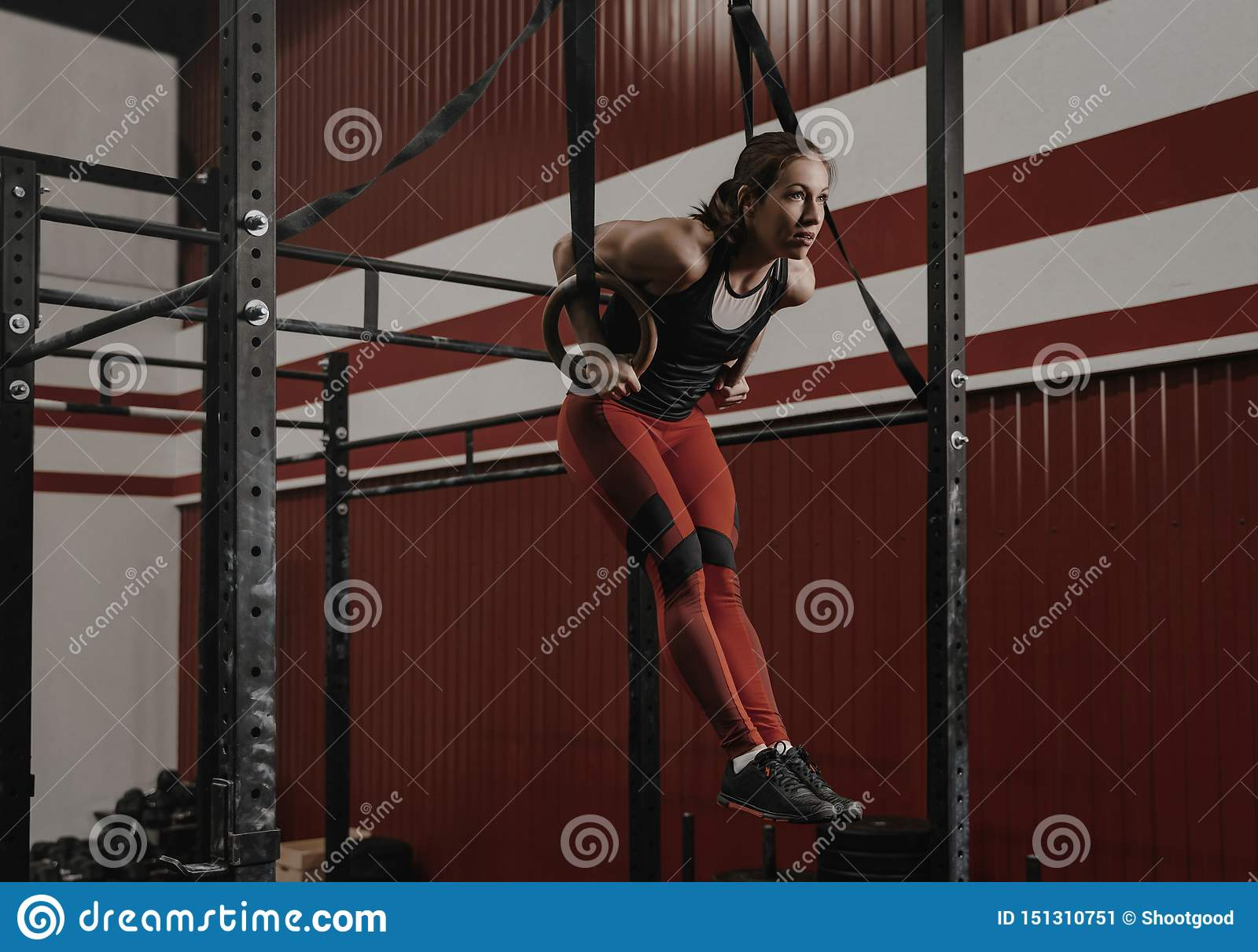 Young crossfit woman doing muscle-ups on gymnastic rings at the gym