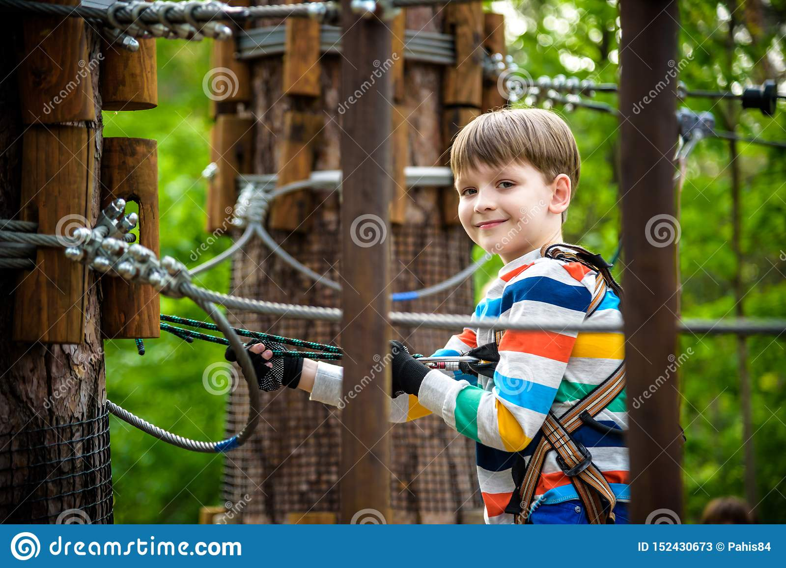 Young cute child boy in summer clothing, safety harness and helmet attached with carbine to cable moves slowly along rope way on