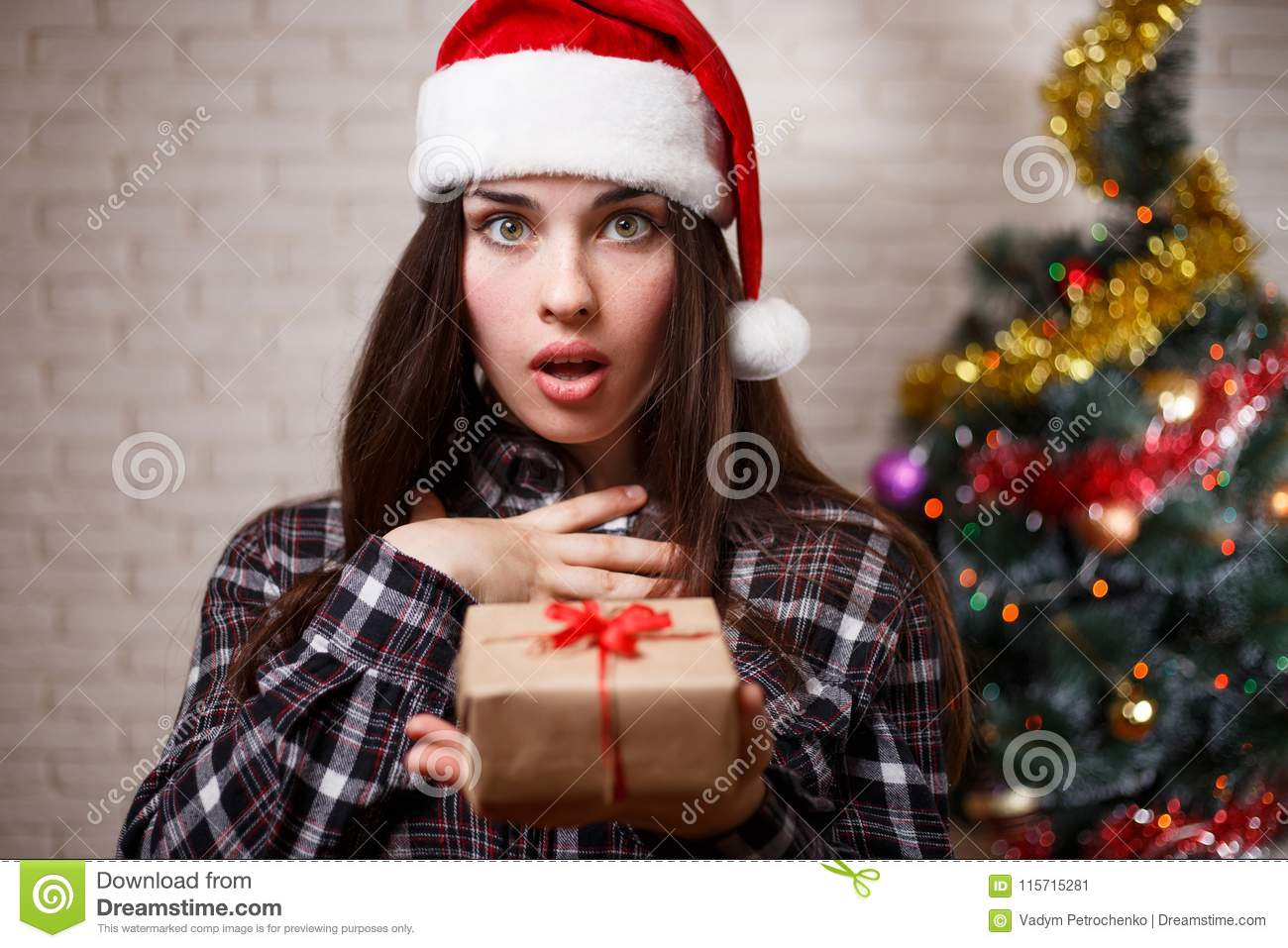 874da56b4b096 Young cute excited woman in Santa cap with a gift box in hand. New Year
