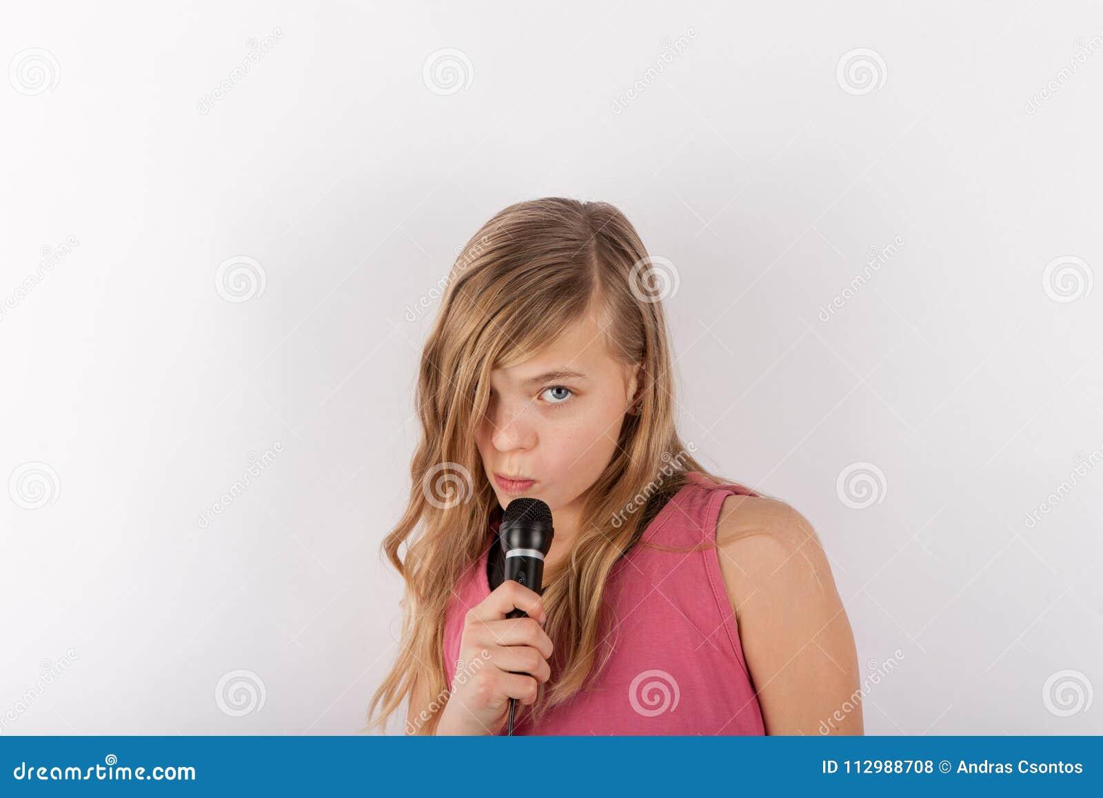 Young cute girl holding a microphone singing karaoke