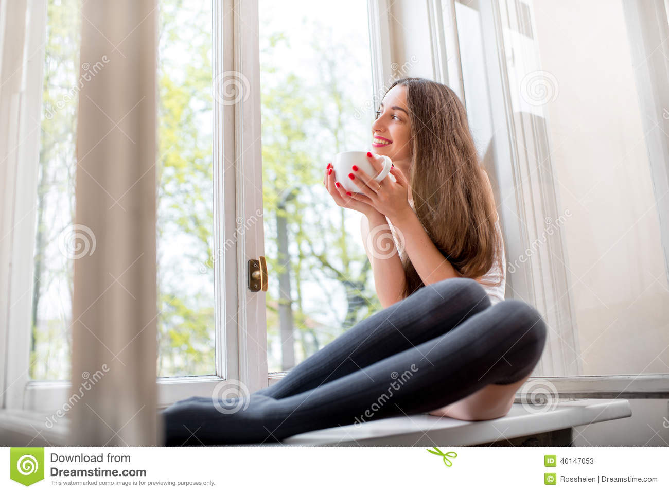Young And Cute Lady Sitting On The Windowsill And Looking