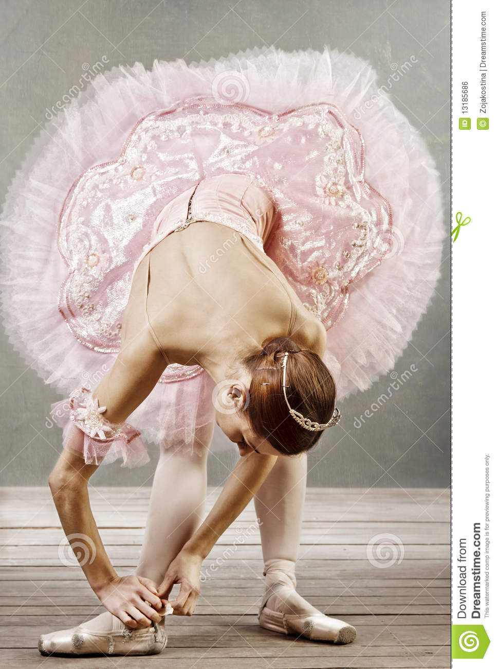 Young dancer fixing her slippers