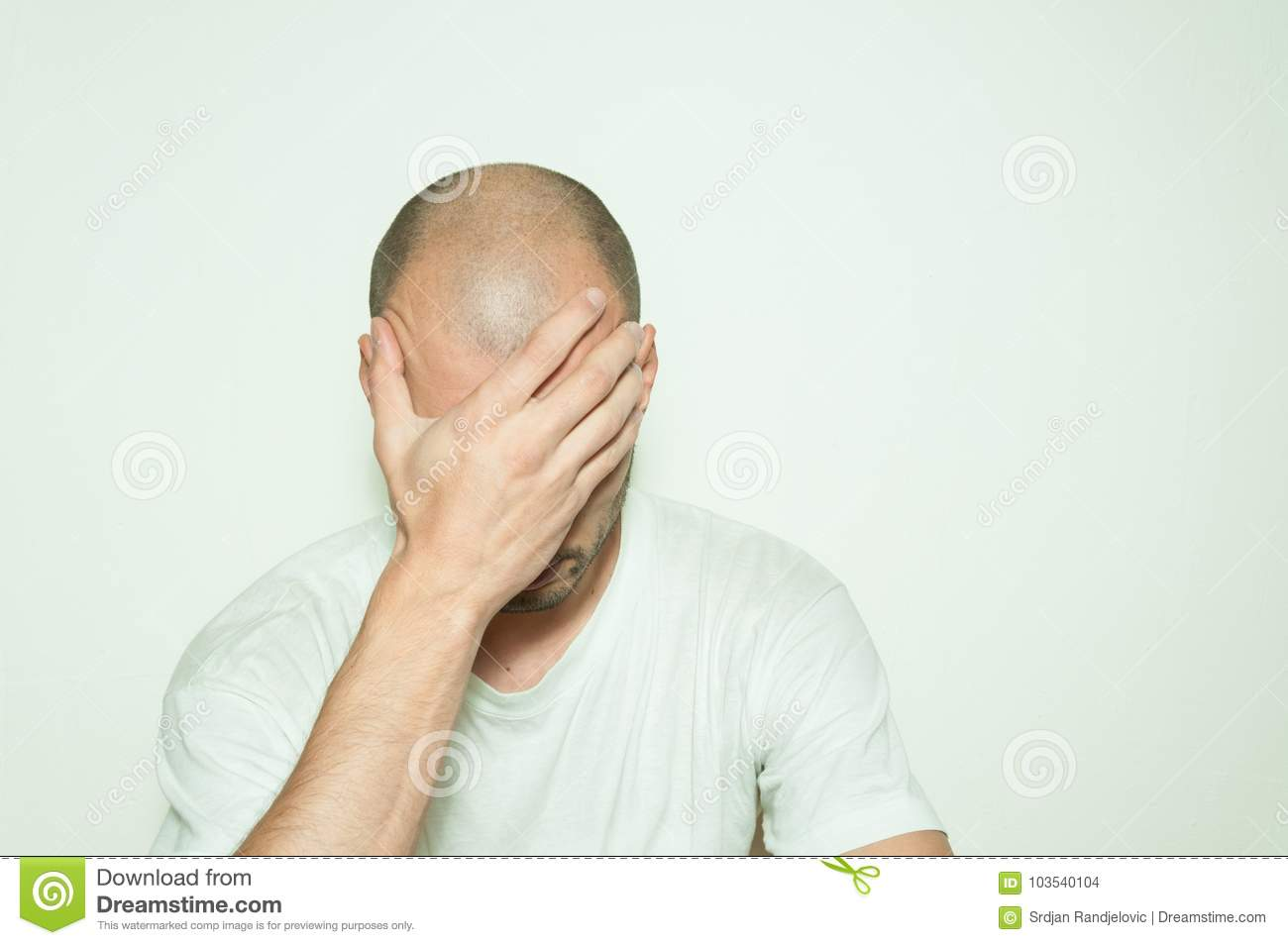 Young depressed man suffering from anxiety and feeling miserable cover his face with his hands and leaning on the white wall.