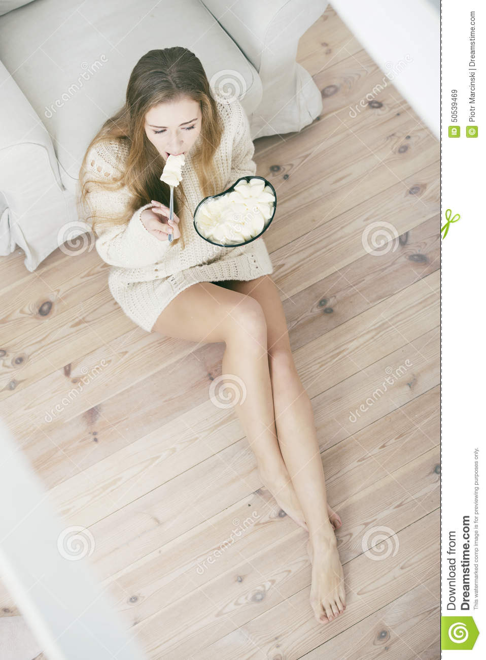 Young depressed woman eating ice cream.