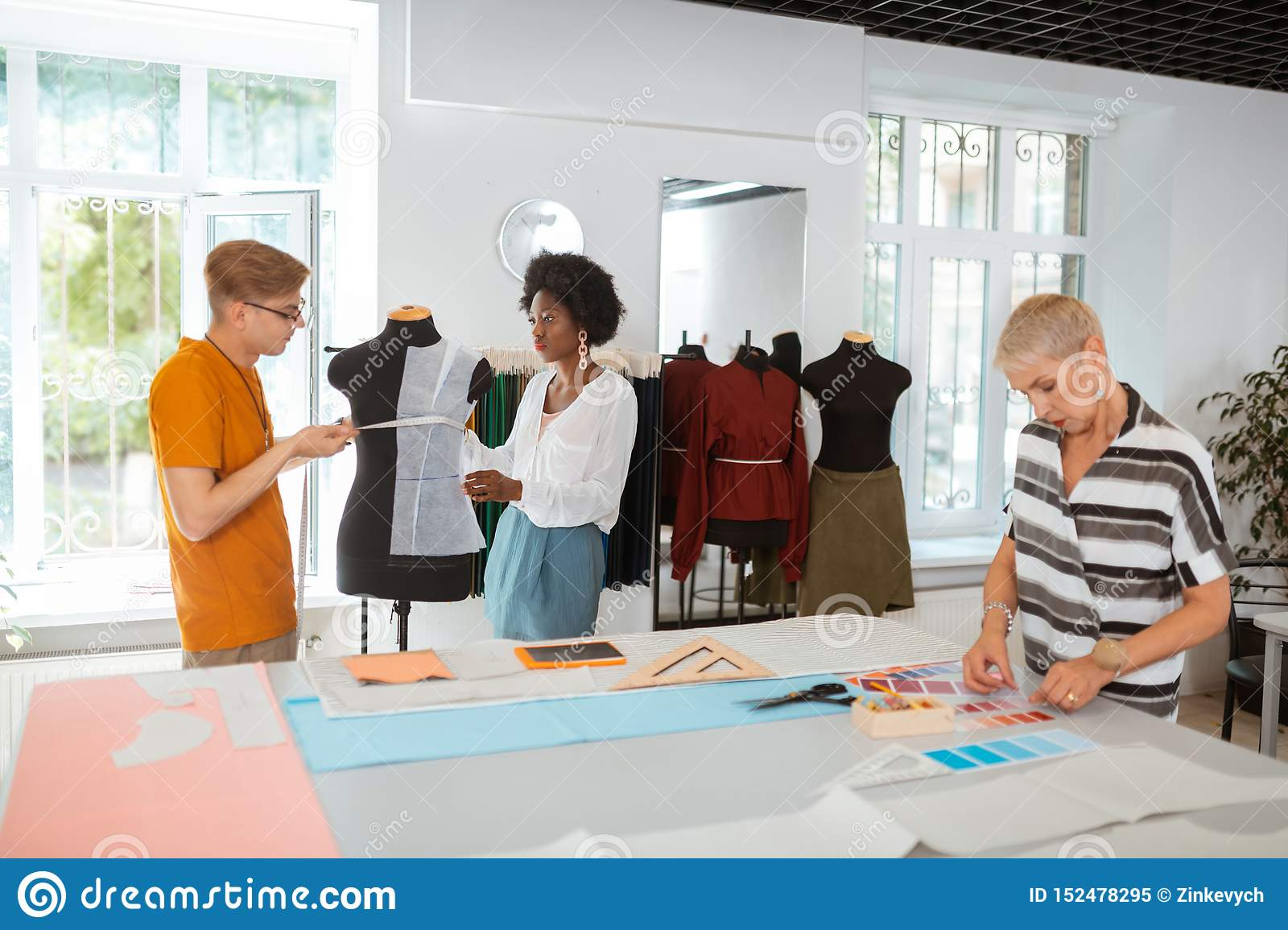 Young designers taking measurements on the tailor dummy