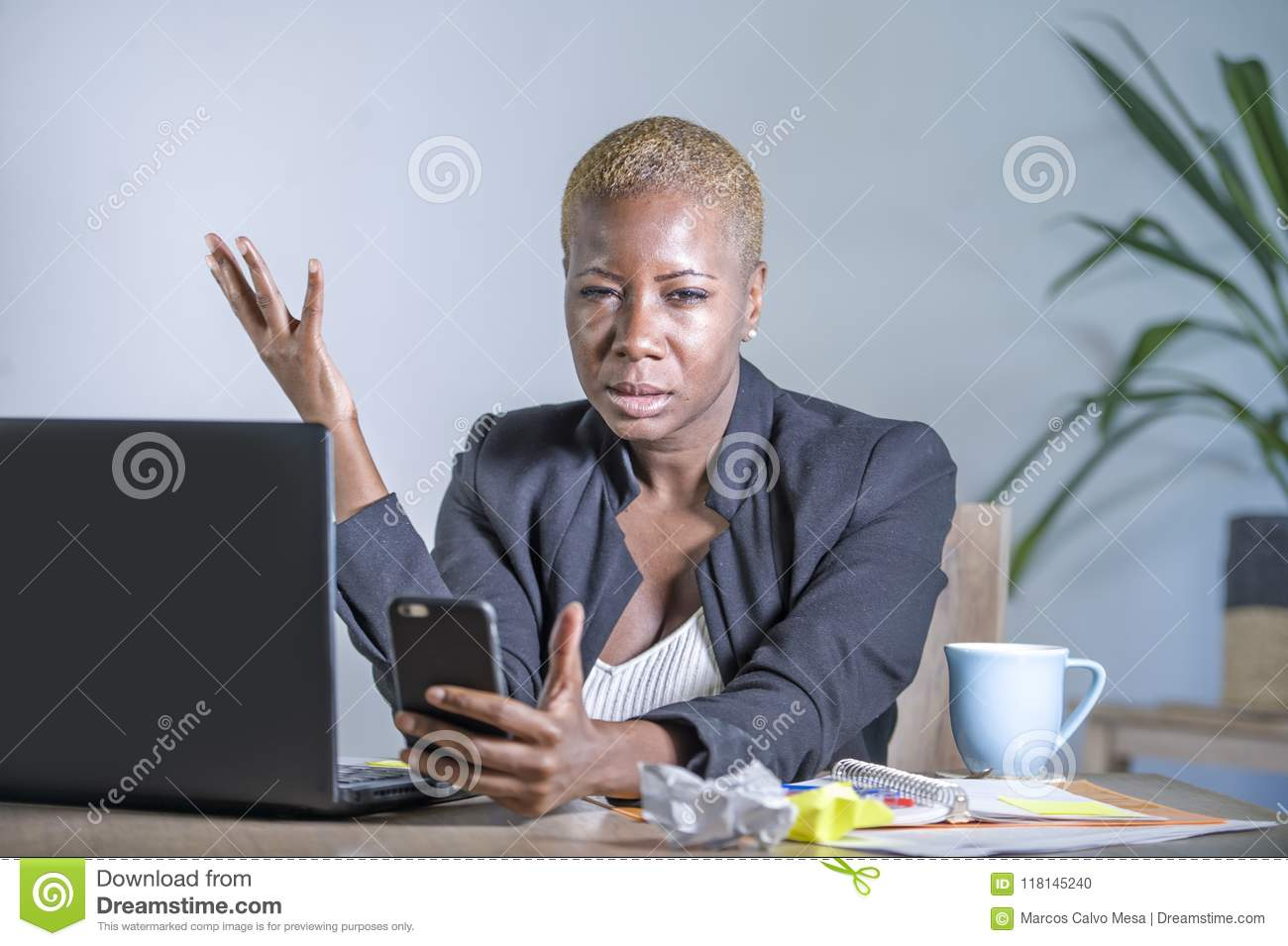 Young desperate and stressed african american business woman working at laptop computer desk at office suffering stress problem us