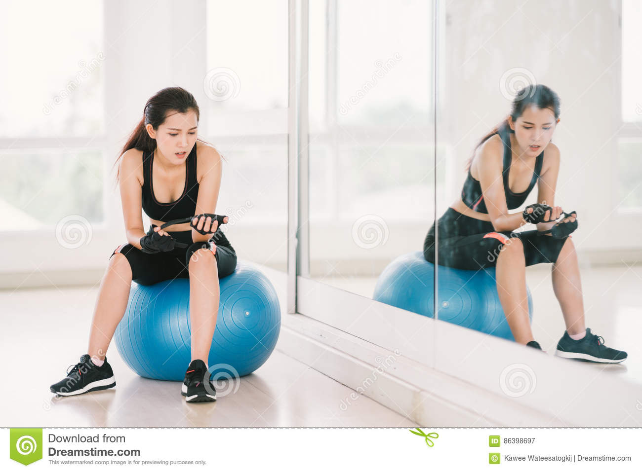 Young and determined Asian girl on fitness ball at gym with mirror, sport and healthy lifestyle concept