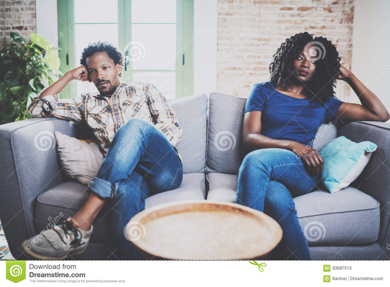 Young displeased black couple.American african men arguing with his stylish girlfriend,who is sitting on sofa on couch