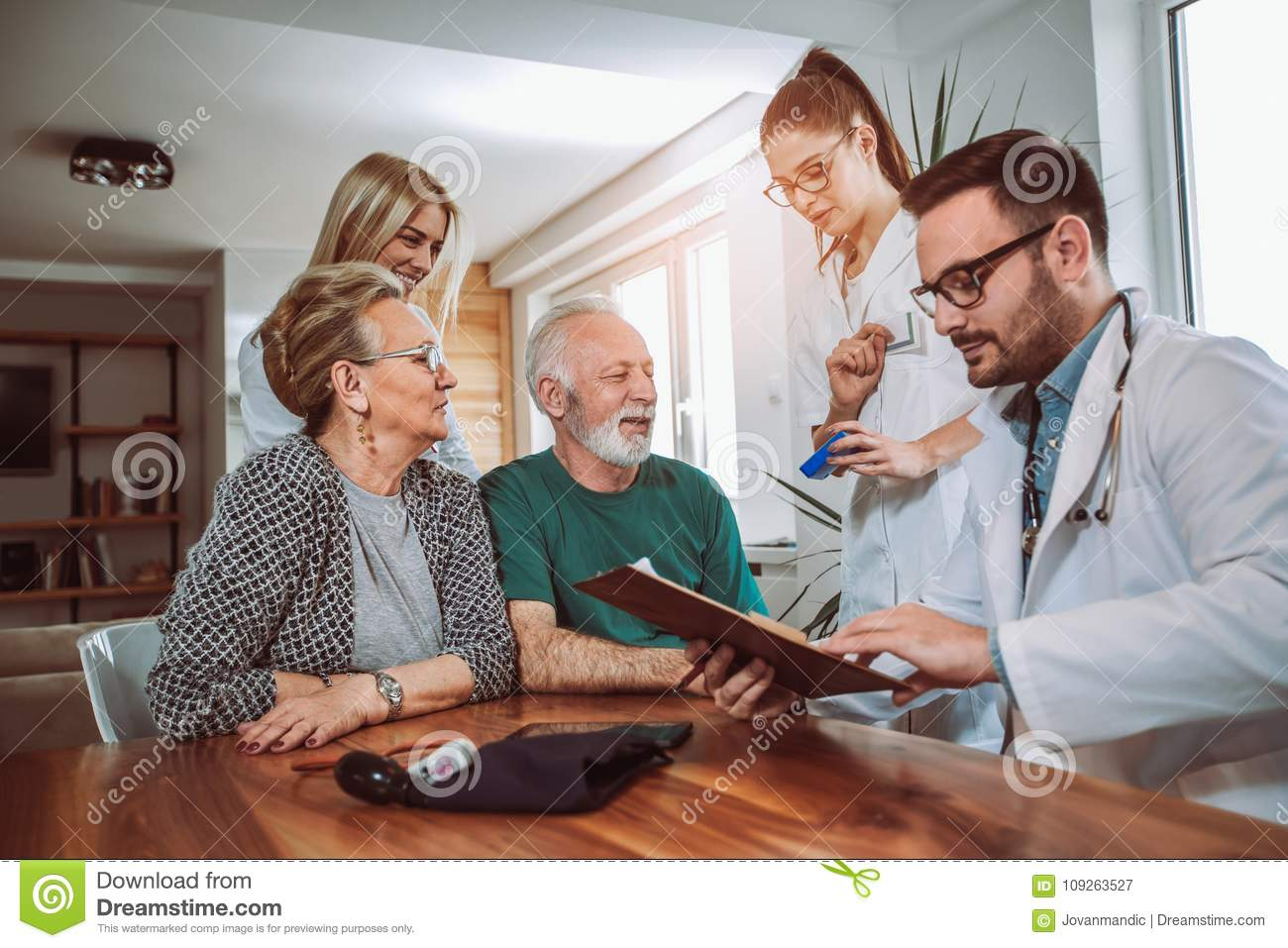 Young doctor during home visit senior people