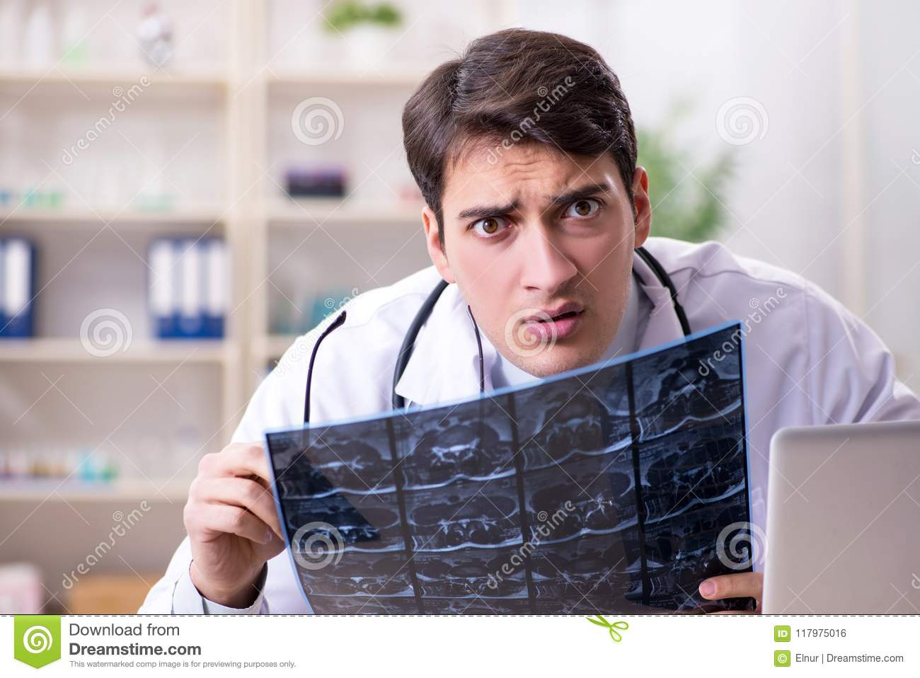 The young doctor looking at x-ray images in clinic