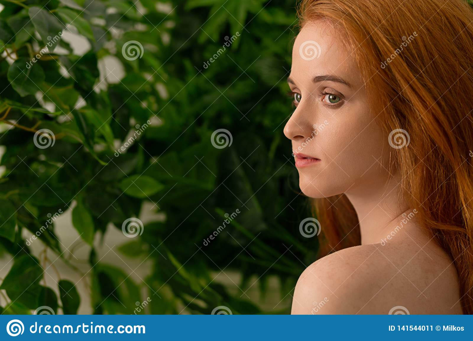 Young dreaming redhead woman at spring garden