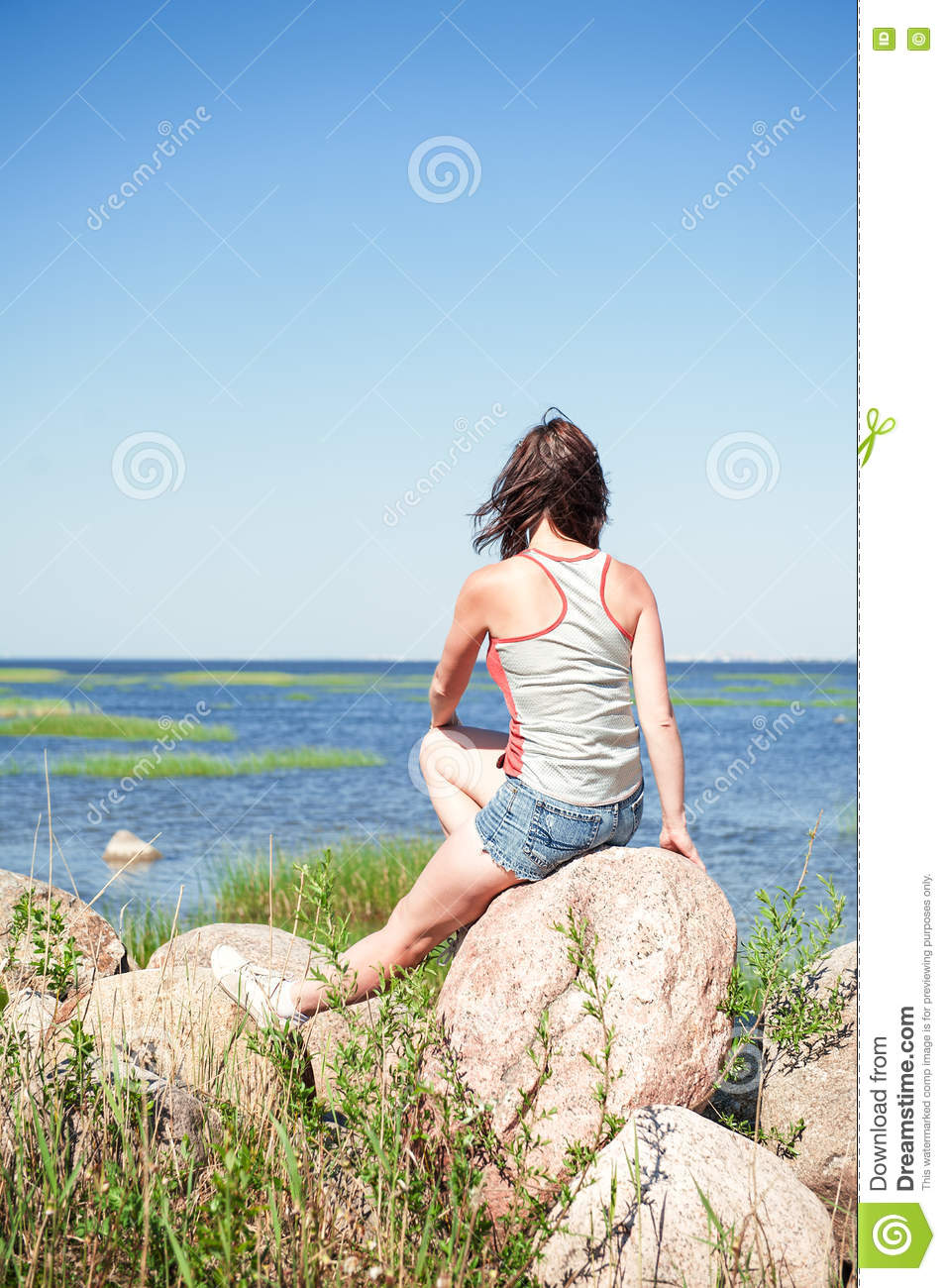 young dreaming woman sitting on the rock facing the sea stock photo